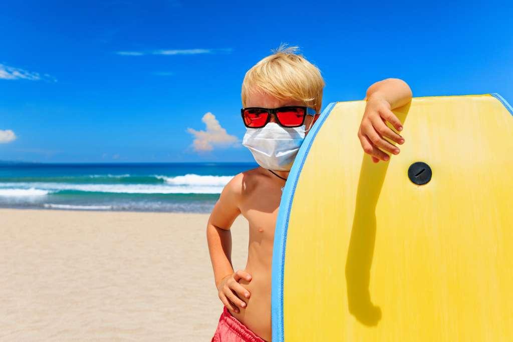 Ni la faible immunité collective ni la chaleur estivale ne parviendront à éradiquer le virus. Ce qui est certain est que le masque sera l'accessoire tendance sur les plages cet été, avec quelques loupés au niveau du bronzage ! © Tropical studio, Adobe Stock
