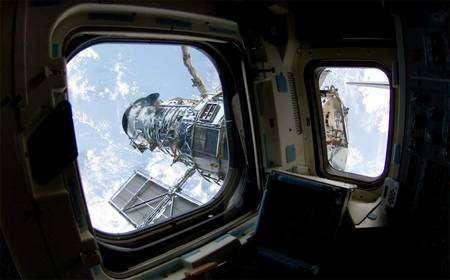 Le télescope spatial Hubble, vu par les hublots d'Atlantis. Crédit Nasa