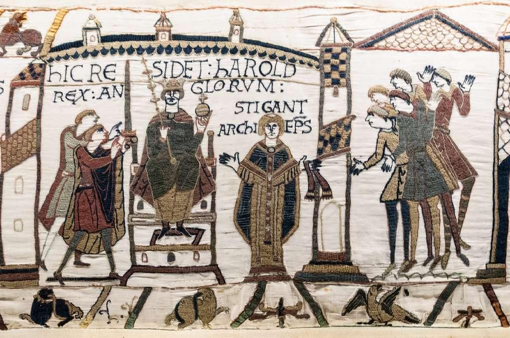 """Tapisserie de Bayeux, scène 30 : couronnement d'Harold roi d'Angleterre, par l'archevêque Stigand en janvier 1066 (""""ici siège Harold, roi des Anglais""""). © Wikimedia Commons, domaine public."""