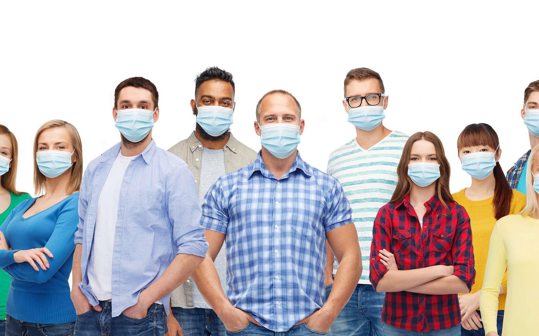 Une nouvelle étude de chercheurs de l'université de Cambridge (Royaume-Uni) conclut que le port généralisé de masques par la population - en plus des mesures de distanciation qui ne sont pas prises sur cette illustration - peut permettre de stopper la propagation du coronavirus et éviter de nouvelles vagues significatives. © Syda Productions, Adobe Stock