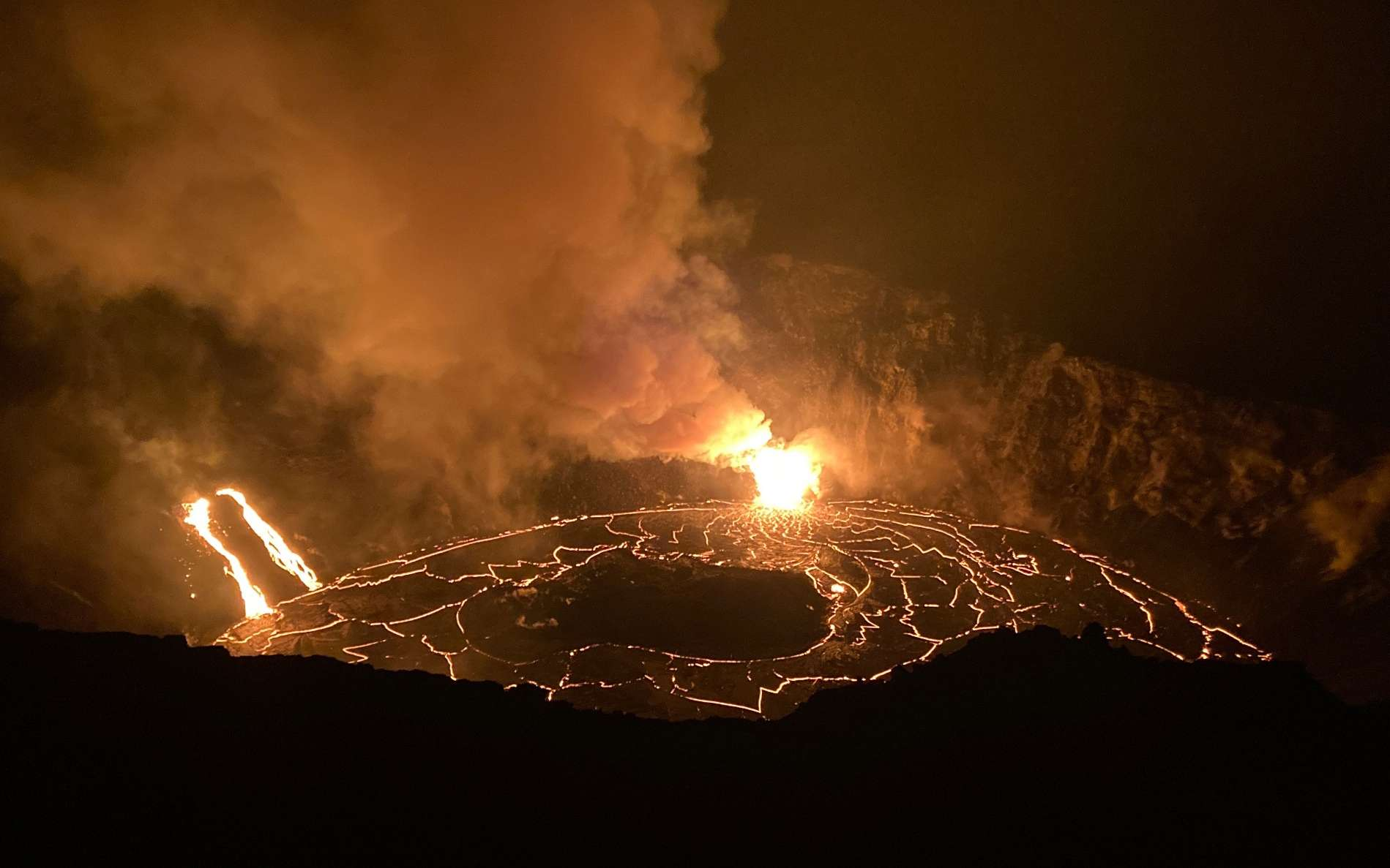 Vers 8 heures, temps local (HST) ce 23 décembre 2020 à Hawaï, les équipes de terrain du HVO ont noté que la surface du lac de lave du sommet du Kīlauea se trouve maintenant à 464 mètres sous le site d'observation du bord du cratère, indiquant que le lac a rempli un volume de 156 m de haut depuis le fond du cratère Halema'uma'u. La profondeur actuelle est plus du triple de la profondeur du lac d'eau qui était dans le cratère jusqu'au soir du 20 décembre 2020 quand il a été vaporisé. Des fontaines de lave se poursuivaient à deux endroits le 23 décembre quand cette photo a été prise vers 5 h 30 HST. © Photo de l'USGS par H. Dietterich.