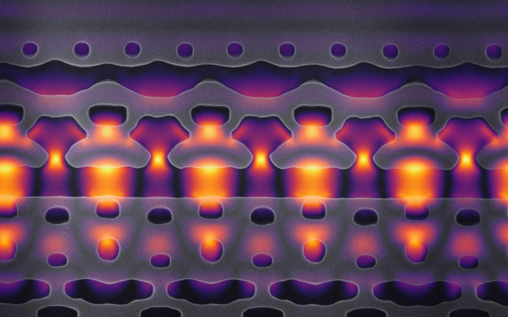 Cette image, agrandie 25.000 fois, montre une section d'un accélérateur sur une puce. Les parties grises concentrent la lumière laser infrarouge (en jaune et en violet) sur les électrons qui circulent dans le canal central. © Neil Sapra