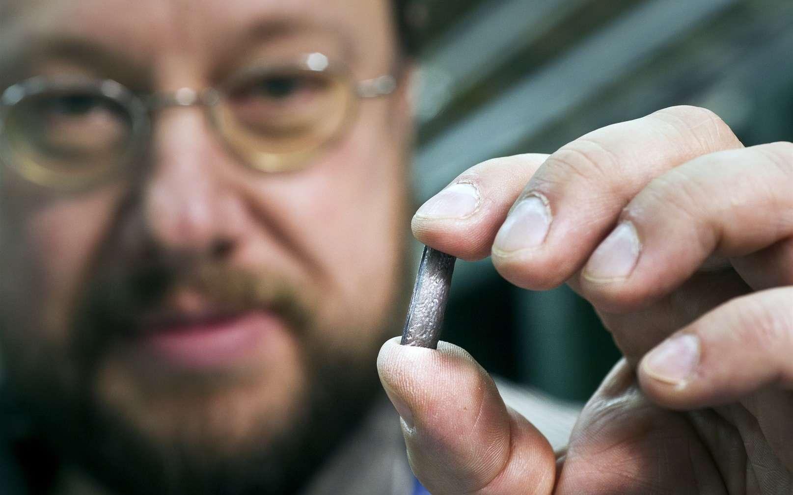 Detlef Kuchler, un physicien du Cern, tient un morceau de la source de plomb utilisée pour créer des ions lourds pour le LHC. © Maximilien Brice - Cern