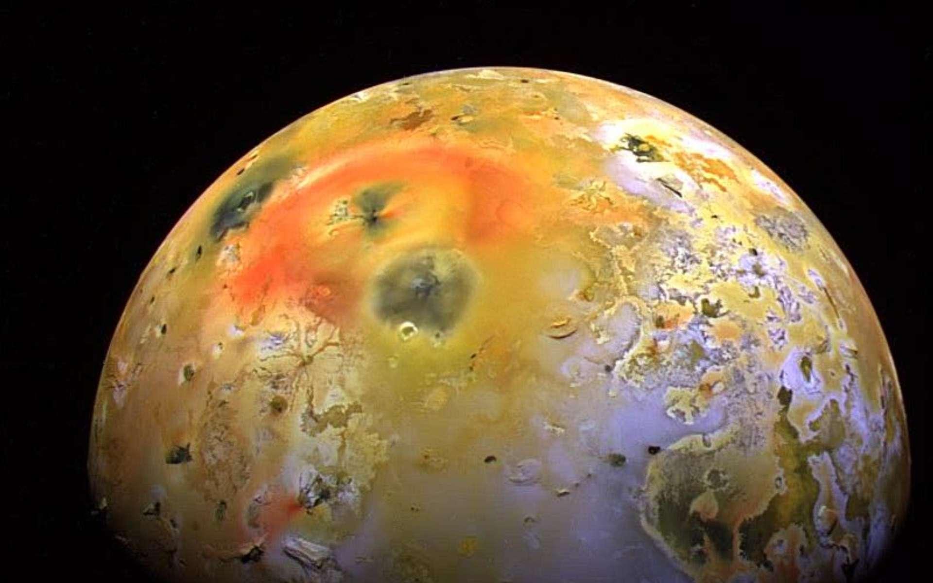 Cette photographie prise par la sonde Galileo montre la tache sombre produite par une éruption à Pillan Patera en 1997. Pillan Patera est une caldeira volcanique d'un diamètre d'environ 73 km nommée d'après le dieu du tonnerre, du feu, et des volcans des Indiens mapuches dans les Andes. Au cours de l'été 1997, une éruption accompagnée de laves à des températures supérieures à 1.600 °C, avec un panache de 140 km de haut, a déposé un matériel pyroclastique noir riche en orthopyroxène sur une zone supérieure à 125.000 km2. C'est la plus importante éruption effusive dont l'Homme a été témoin, avec au moins 31 km3 de laves émises sur une période de 100 jours. L'éruption a produit un large dépôt de matière sombre de 400 km de diamètre, qui recouvre partiellement l'anneau de dépôts couleur rouge vif entourant le volcan Pélé. © Nasa, JPL, University of Arizona