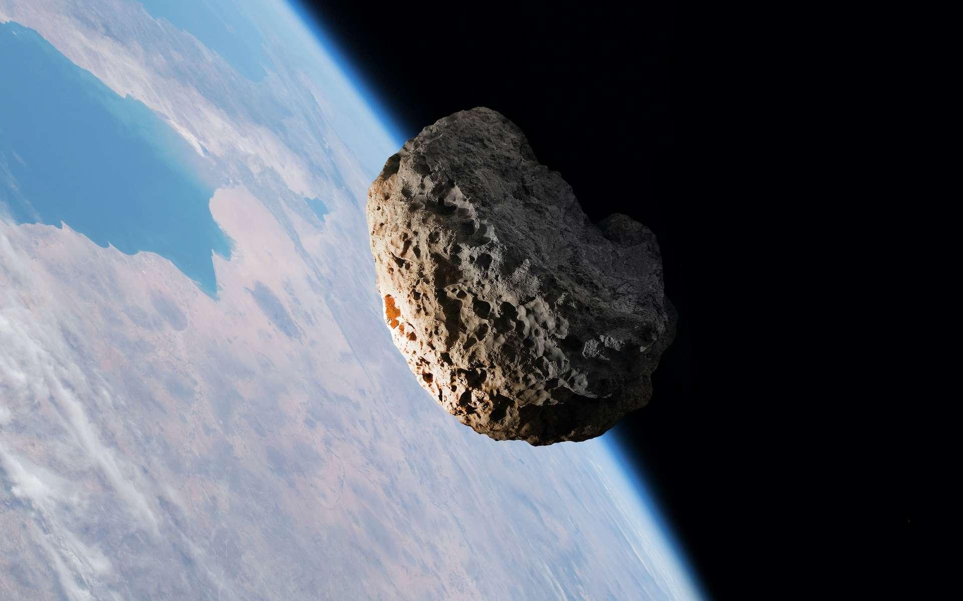 Illustration d'un astéroïde survolant la Terre. © tangoas, Adobe Stock