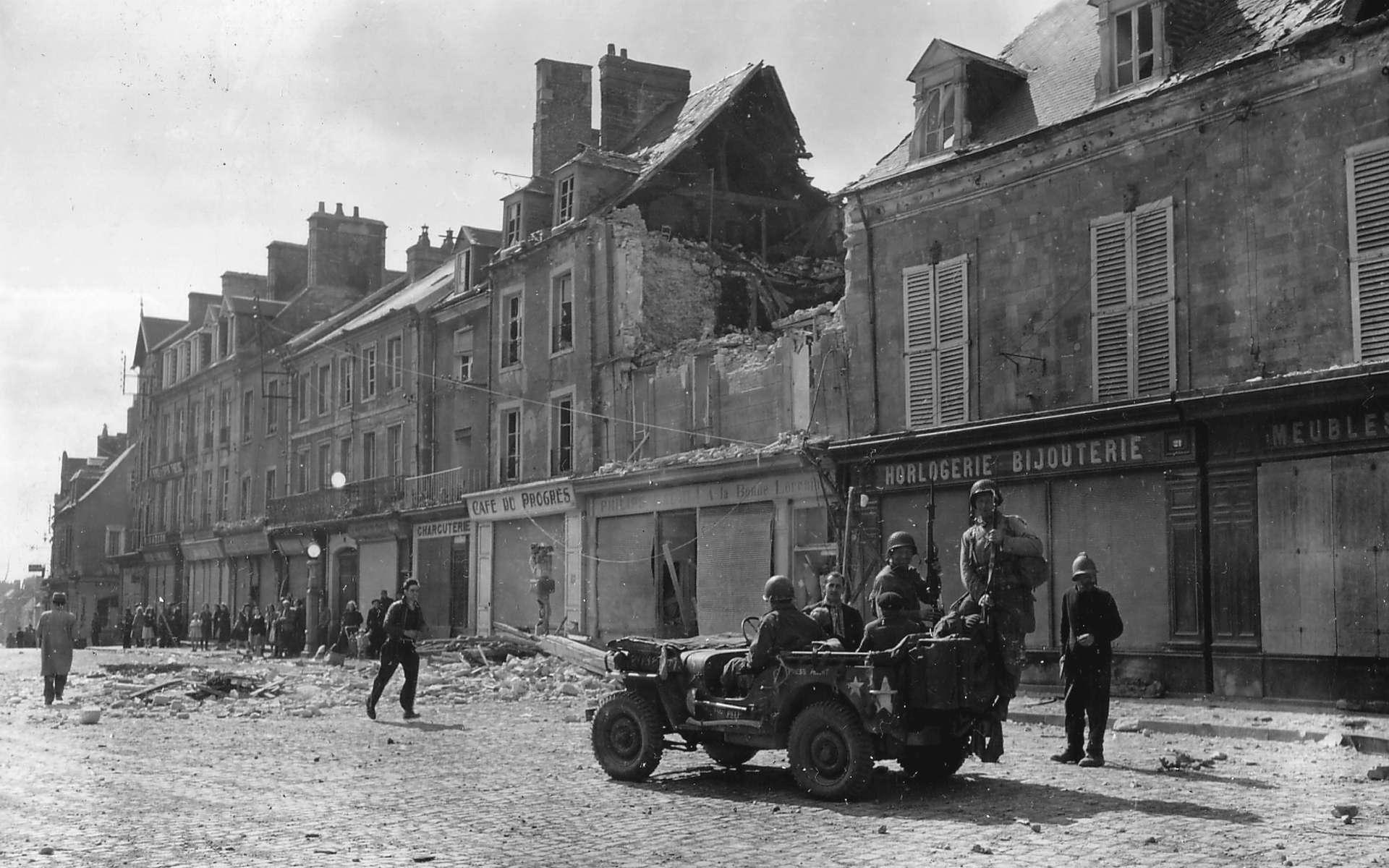 Trois soldats américains, place de la République à Carentan, Normandie. © Conseil Régional de Basse-Normandie/National Archives USA