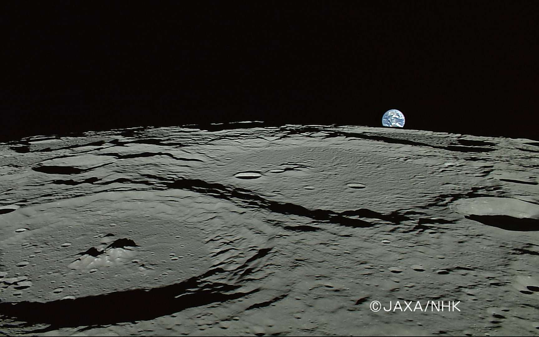 Au premier plan à gauche, le cratère Plaskett (82,1N/174,3E, diamètre : 109 km) et au second plan le crétère Rozhdestvenskiy (85,2N/155,4W, diamètre : 177 km). Cette image a été prise le 5 avril 2008 par la caméra HD de la NHK équipant Kaguya-Selene. La Terre est visible à l'horizon. Crédit : Jaxa/NHK