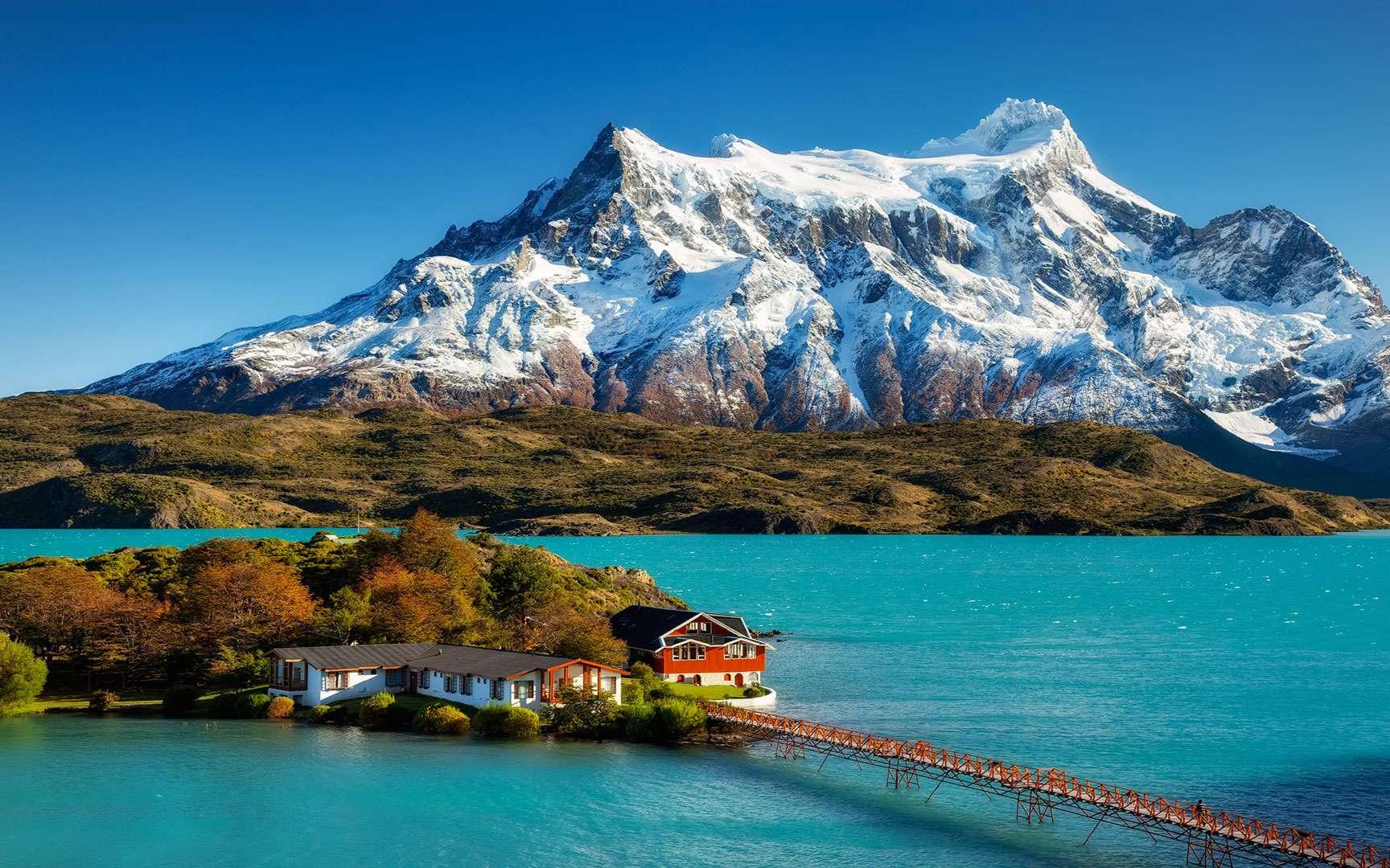 Un ciel bleu comme on n'en voit pas si souvent. Une montagne aux reflets blancs qui se dresse fièrement devant nous. Une dense végétation à son pied. Un lac aux eaux turquoise. Et sur une petite île, uniquement reliée à la terre par une passerelle piétonne, deux charmantes maisons dans lesquelles on aimerait passer quelques jours de vacances, loin du monde… La Patagonie, c'est ça et bien d'autres paysages incroyables de naturel et de quiétude. © Marcio Cabral