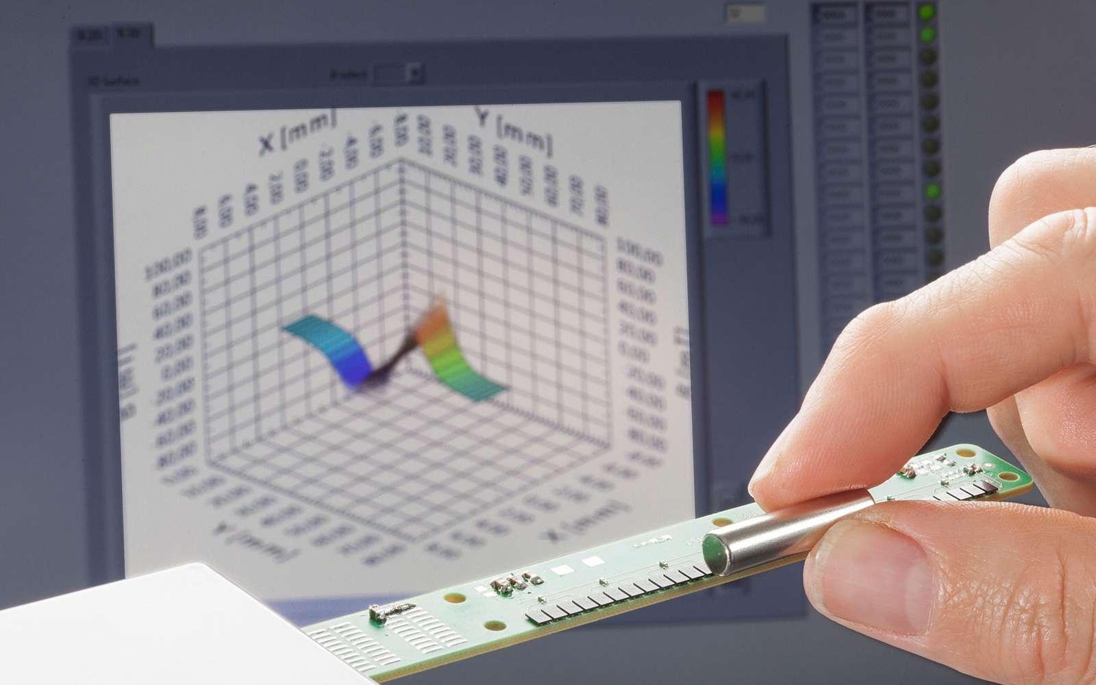 La caméra en ligne (au premier plan) mesure en temps réel les propriétés d'un champ magnétique. Les données enregistrées sont ensuite traduites, non pas en une véritable image, mais sous la forme d'un graphique (ici à l'arrière-plan). Celui-ci permet de visualiser les variations du champ magnétique étudié suivant les trois dimensions de l'espace. © Max Etzold