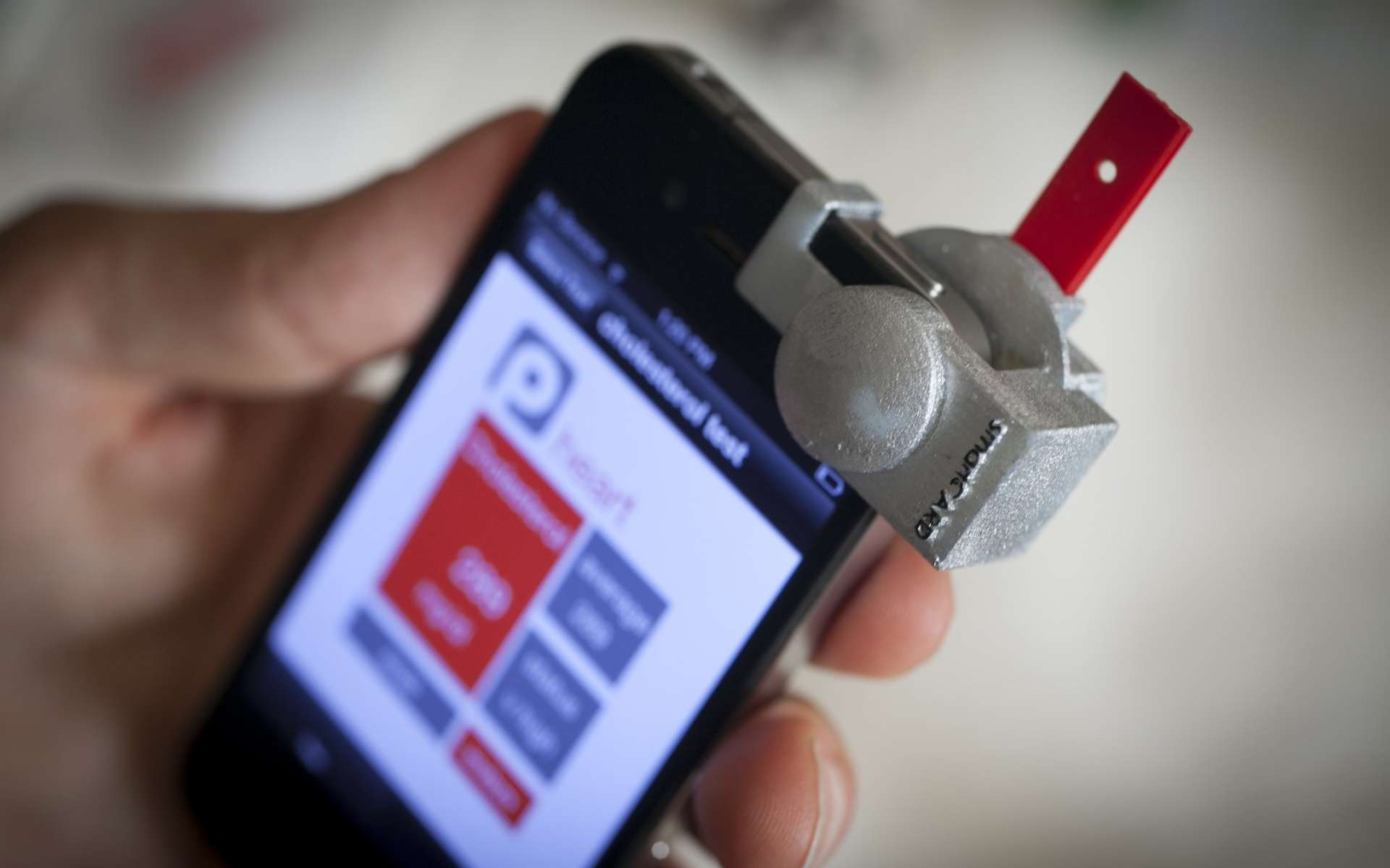 Après avoir déposé une goutte de sang sur la plaquette rouge, l'utilisateur l'introduit dans le boîtier SmartCard, fixé sur le smartphone devant l'appareil photo, et lance l'application. Voilà comment mesurer le taux de cholestérol aussi facilement qu'un diabétique surveille sa glycémie. © Université Cornell