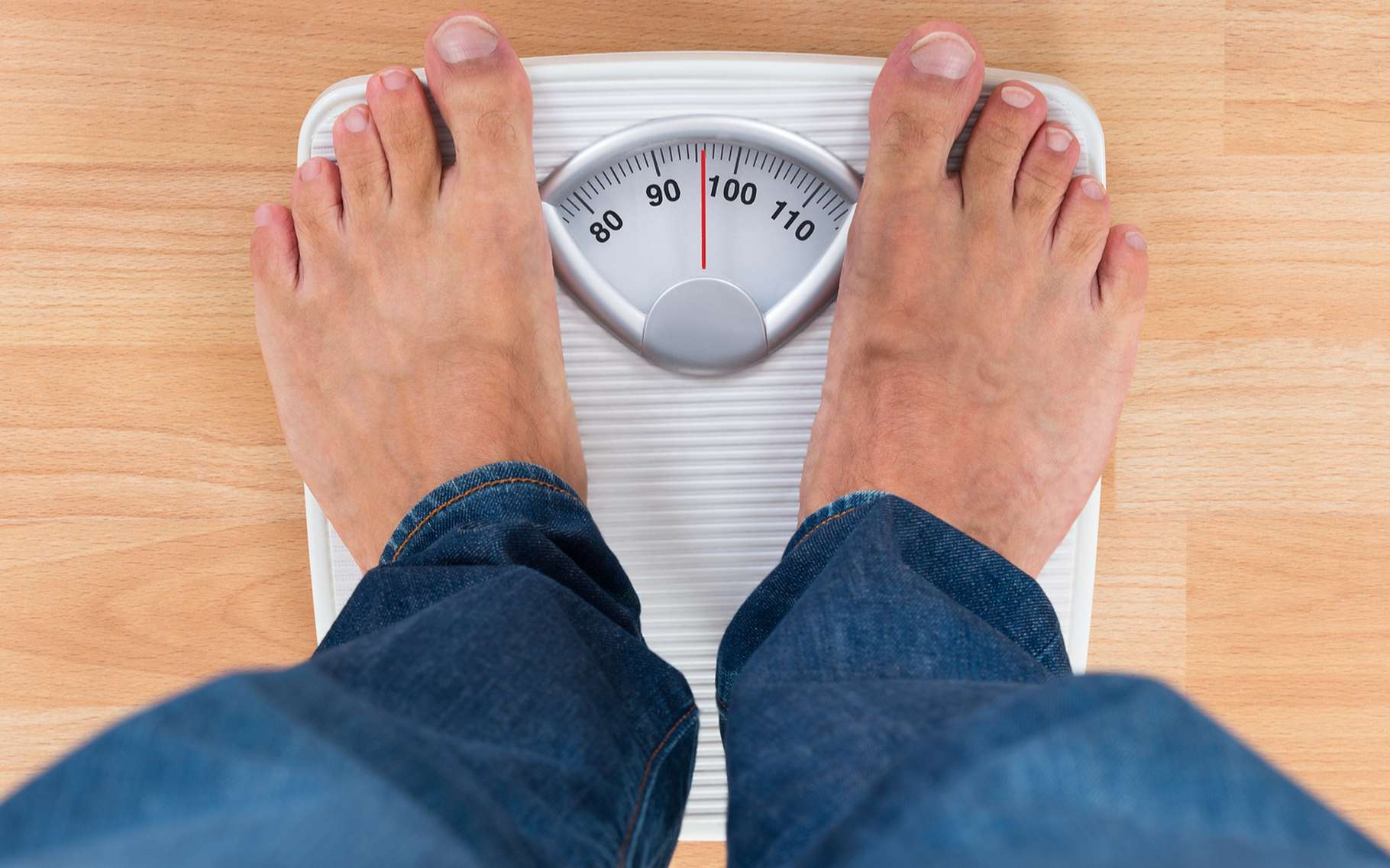 Un pèse-personne indique le poids, mais comme il est calibré pour fonctionner sur Terre, ce poids est automatique traduit en kilogrammes, soit en une masse. © Andery_popov, Shutterstock
