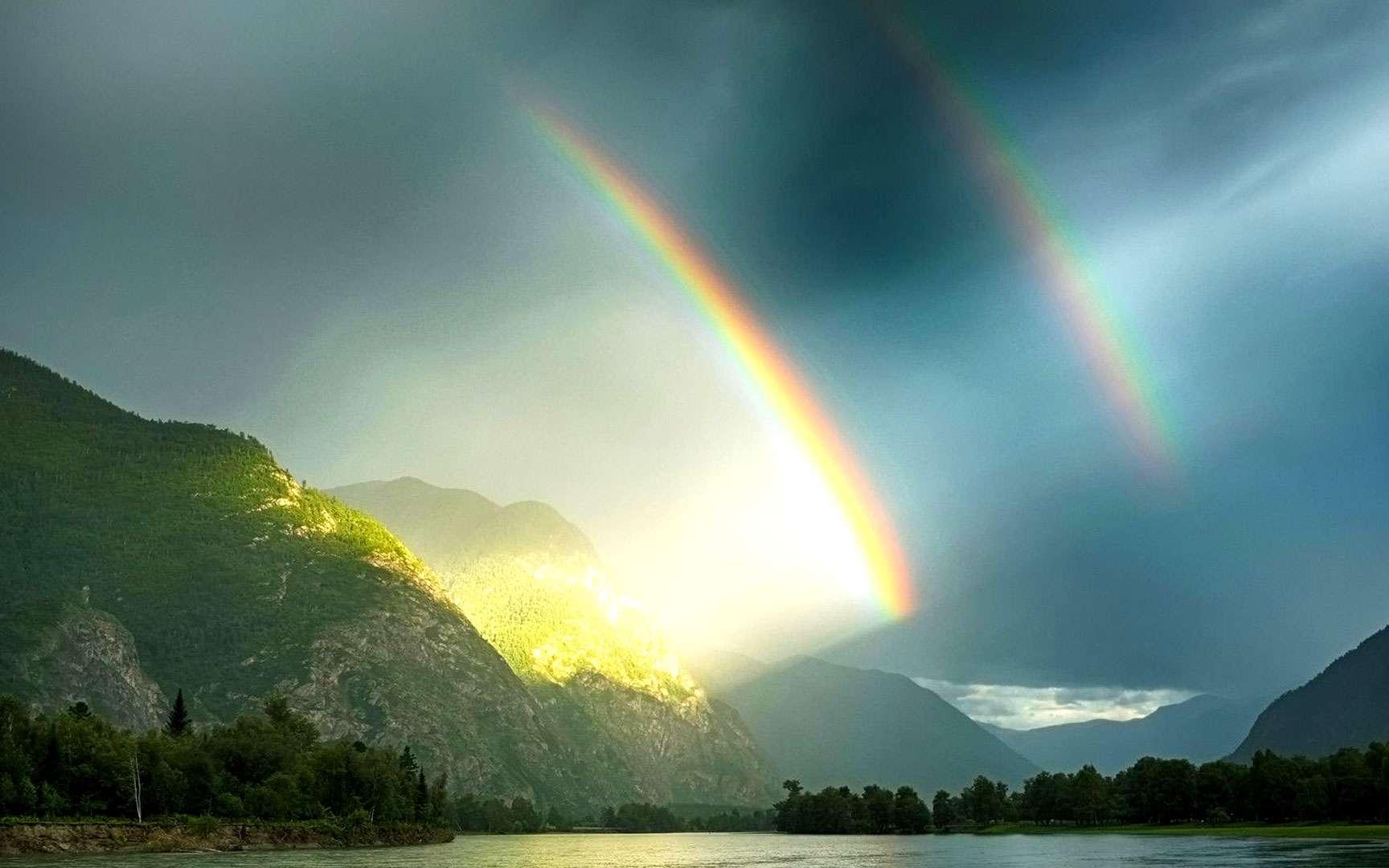 Arc-en-ciel primaire et arc-en-ciel secondaire. Cette photo a été prise dans la région montagneuse de l'Altaï située entre la Russie, la Chine, la Mongolie et le Kazakhstan. Il est possible d'y voir un arc-en-ciel primaire et un arc-en-ciel secondaire. L'arc-en-ciel primaire est le plus coloré. Le deuxième arc, moins visible, est l'arc-en-ciel secondaire. Ce dernier n'est pas tout le temps visible mais est en fait toujours présent. Les couleurs de l'arc secondaire sont inversées par rapport à celles du premier arc. © moonglee, Shutterstock