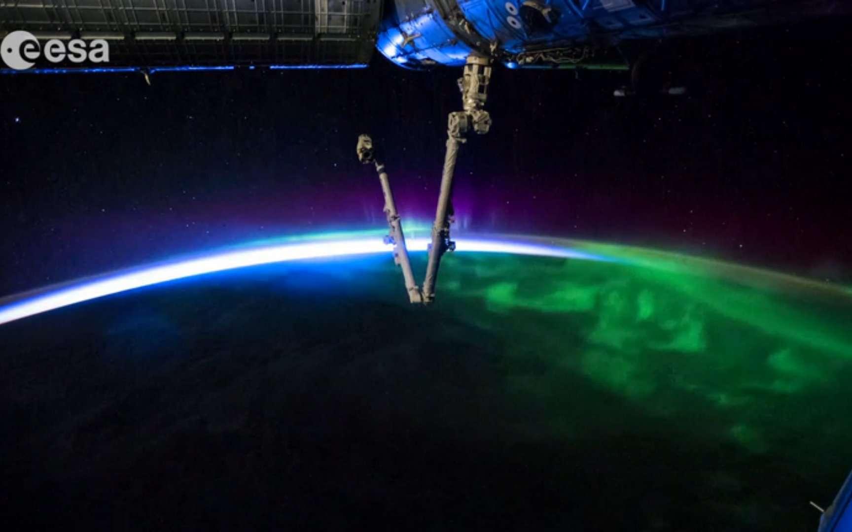 Des aurores polaires cèdent la place au lever du Soleil sous le bras robotisé Canadarm de la Station spatiale internationale. De quoi donner envie de s'installer dans l'ISS pour quelques jours de vacances contemplatives... © Esa