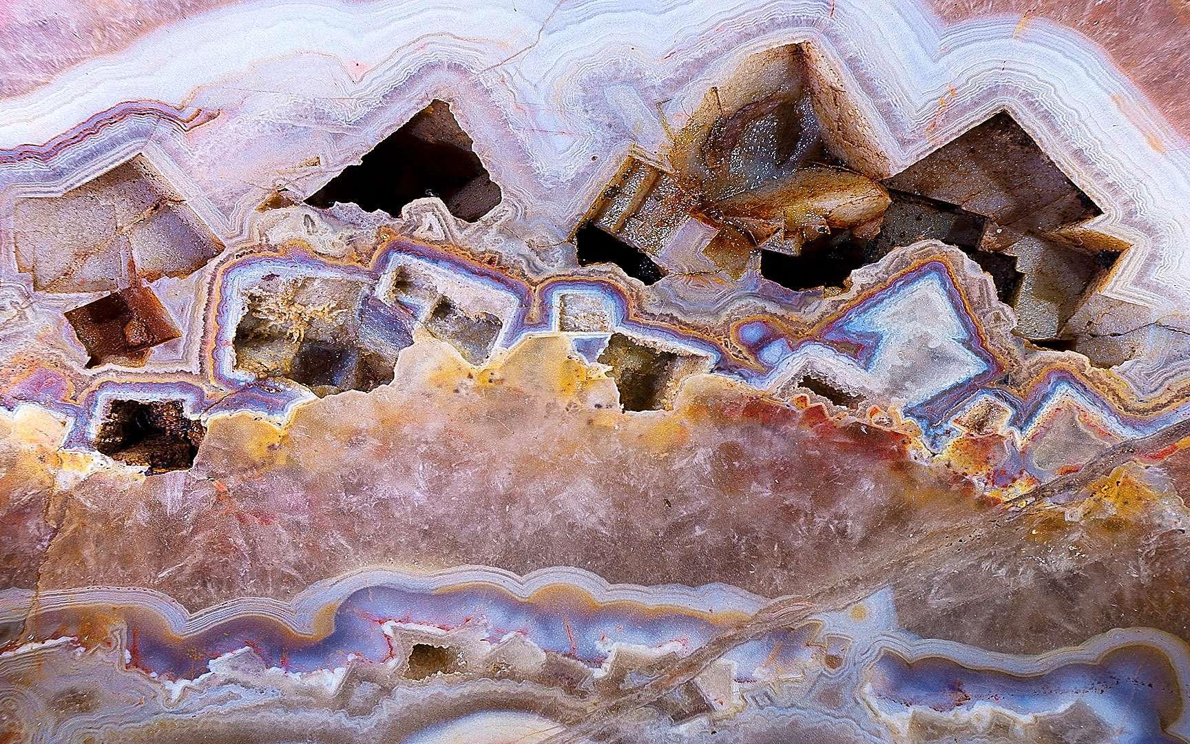 Agate du Brésil, résistante et poreuse. L'agate est une matière composée de silice et colorée par des oxydes. C'est une calcédoine ou quartz polycristallin. En fonction de leur aspect, les agates ont reçu des noms évocateurs : agate mousse, agate rubanée, agate œillée, agate festonnée, agate plume, agate arborisée, agate paysage. Caractéristiques : dureté : 6,5 à 7 échelles de Mohs/10; densité : 2.58-2.65 ; composition : SiO2 ;classe cristalline : quartz ; variété : calcédoine ;système cristallin : trigonal/microcristallin ; propriétés optiques : indice de réfraction : 1.530-1.540 ; biréfringence : 0,009 à 0.004 ; signe optique : biaxe positif ; polychroïsme : néant. Entretien : pas d'entretien particulier. Eau savonneuse. Traitement : les caractéristiques physiques des agates, à la fois résistantes et poreuses, ont facilité depuis longtemps leur traitement. Le premier témoignage de Pline décrivait la coloration en noir des agates pour leur donner l'aspect de l'onyx, plus prisé. Le traitement thermique des agates accentue les teintes allant de l'orangé au rouge. La teinture : plusieurs procédés sont utilisés. Après un choc thermique ou chimique, l'agate acceptera plus facilement la teinture sous forme d'encre ou de colorant. Après une montée en température dans du bicarbonate HCO3, une solution chimique donnera la teinte : noir : sucre puis acide sulfurique (2H3O) + (SO42) ;brun : sucre + traitement thermique ; bleu : réaction de la potasse sur du sulfate de fer : potasse de prusse jaune + sulfate de fer ; vert : Acide de chrome H2CrO4 ou nitrate de nickel (Ni(NO3)2, 6H2O) ;rouge : nitrate de fer Fe(NO3). © Bruno Cupillard, aventures-cristallines.fr, tous droits réservés.