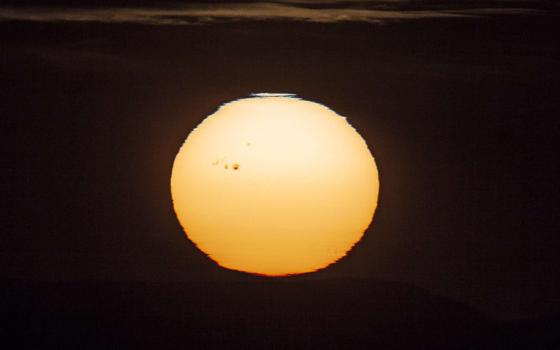 Un immense groupe de taches sombres macule la surface du Soleil, photographiée lors du coucher de l'astre du jour. Attention, il ne faut jamais regarder directement le Soleil sans protection adaptée. © Jürg Alean