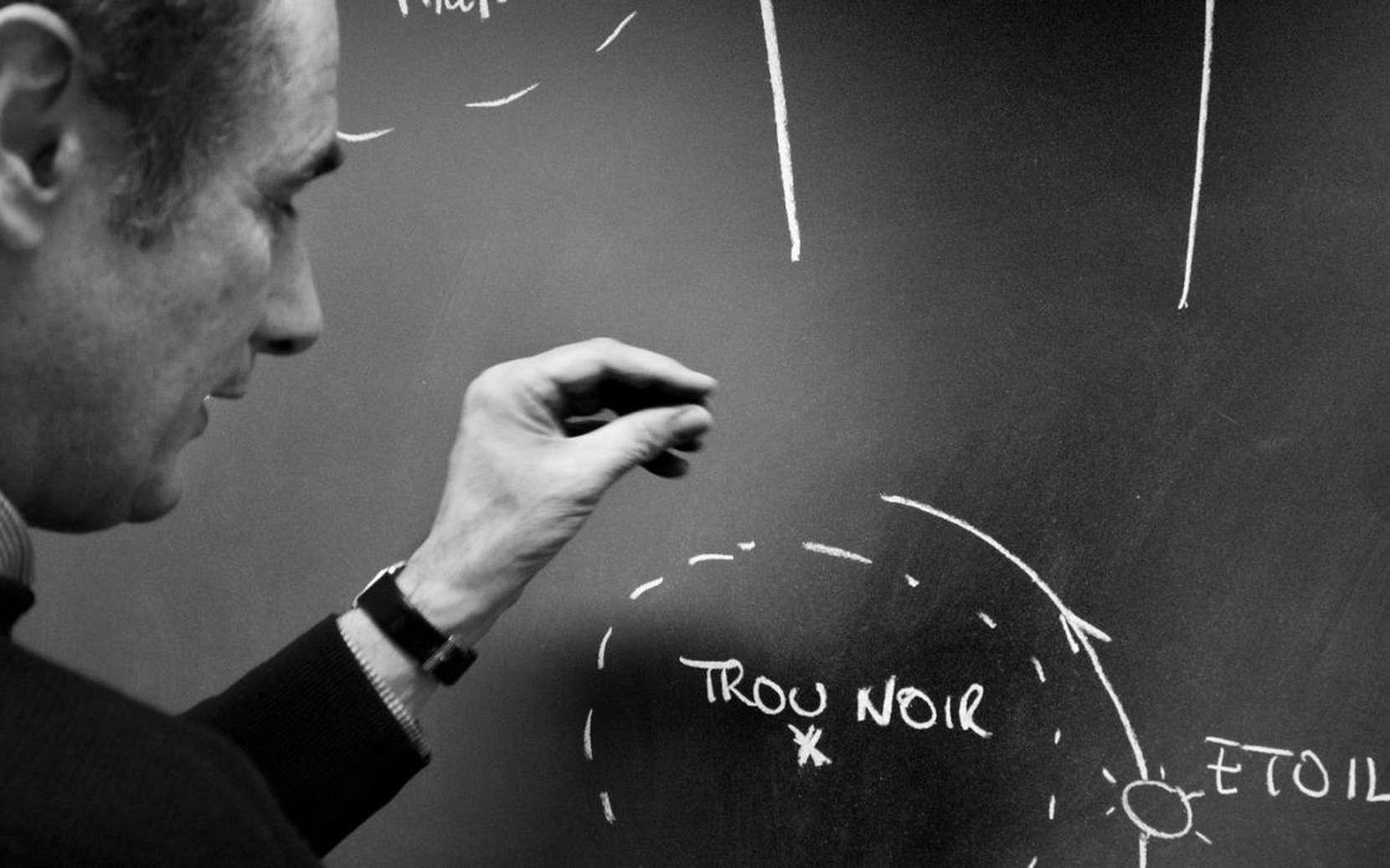 Pierre Binétruy au tableau noir, expliquant l'intérêt d'une source particulièrement fascinante d'ondes gravitationnelles, un astre , étoile à neutrons ou trou noir stellaire, sur le point de fusionner avec un trou noir supermassif. © dars et papillault