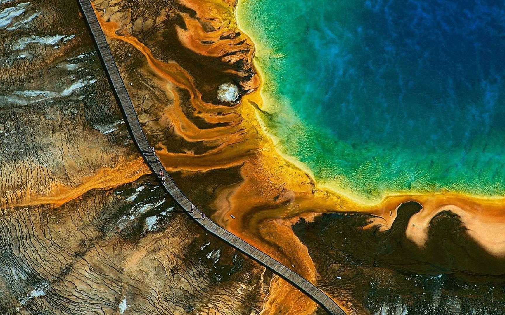 Etats Unis - Parc de Yellowstone. Etats Unis : Geyser du grand prismatic, parc national de Yellowstone, Wyoming - Situé sur un plateau volcanique qui chevauche les États du Montana, de l'Idaho et du Wyoming, Yellowstone est le plus ancien parc national du monde. Créé en 1872, il s'étend sur 9 000 km2 et présente la plus grande concentration de sites géothermiques du globe, avec plus de 10 000 geysers, fumerolles et sources chaudes. D'un diamètre de 112 m, le Grand Prismatic Spring est le bassin thermal le plus vaste du parc, et le troisième au monde par sa taille. Le spectre de couleurs qui lui a valu son nom est dû à la présence d'algues microscopiques dont la croissance dans l'eau chaude, au cœur de la vasque, diffère de celle de la périphérie où la température est moins élevée. Réserve de Biosphère depuis 1976, inscrit sur la Liste du patrimoine mondial de l'Unesco en 1978, le parc national de Yellowstone reçoit en moyenne 3 millions de visiteurs chaque année. Le continent nord-américain, où sont situés les cinq sites naturels les plus fréquentés du monde, accueille annuellement plus de 70 millions de touristes (1/10 du tourisme mondial), qui lui apportent 1/5 des recettes mondiales de l'activité touristique. © Photo Yann Arthus-Bertrand - Tous droits réservés http://www.yannarthusbertrand.com/index_new.htm