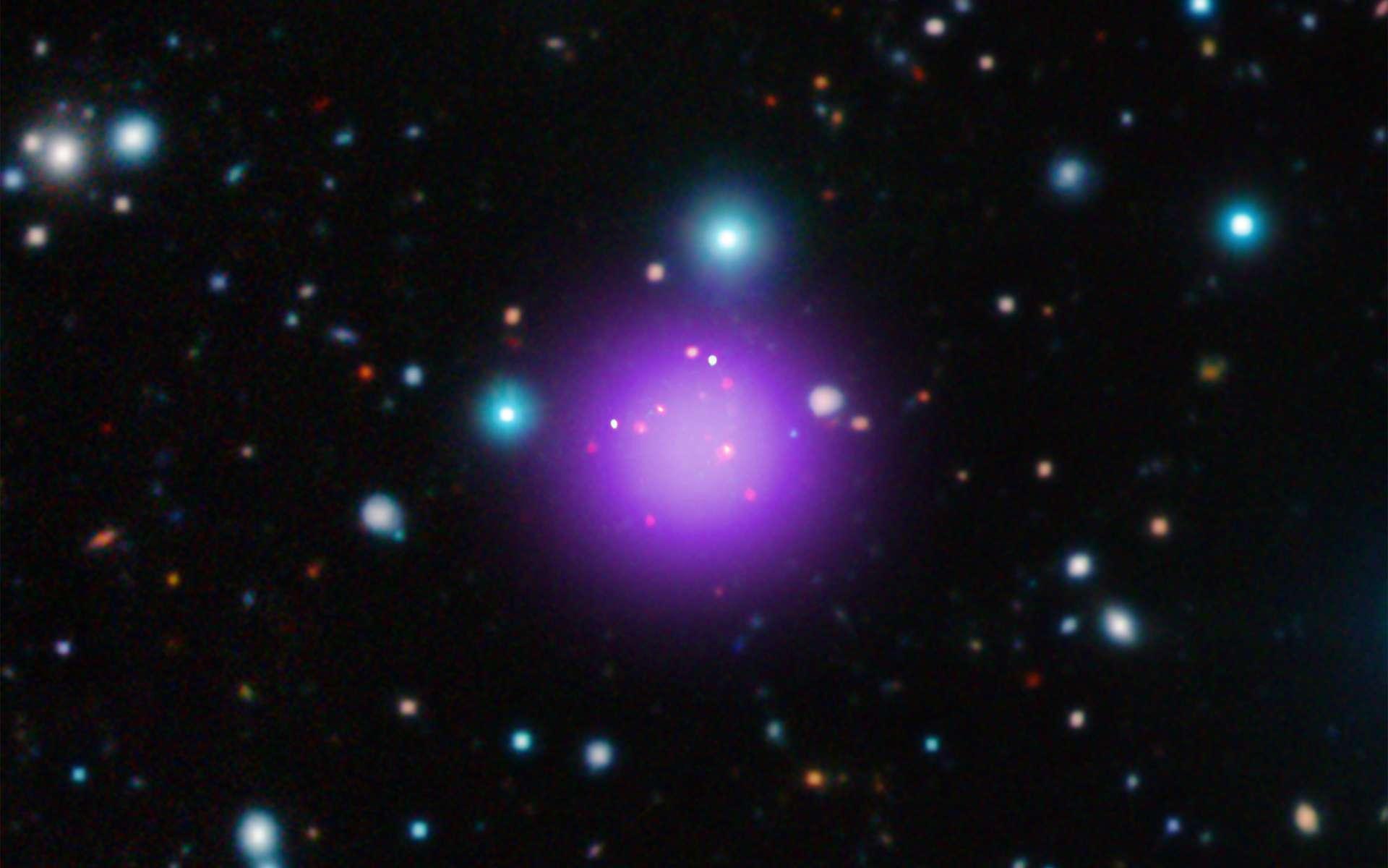 Les amas de galaxies tels que CL J1001+0220, qui est donc l'amas le plus lointain connu, constituent les plus grandes accumulations de matière soudées par la gravitation qui sont nées depuis le Big Bang. Selon le scénario accepté de formation hiérarchique des structures, ces amas se seraient formés en dernier, après les étoiles puis les galaxies. L'image montre en violet l'émission de rayons X, captée par le satellite Chandra. Ceux-ci sont issus de la matière située entre les galaxies et qui est chauffée à plusieurs millions de degrés par l'énorme gravité de l'amas. © X-ray : NASA/CXC/Université Paris/T.Wang et al ; Infrared : ESO/UltraVISTA ; Radio : ESO/NAOJ/NRAO/ALMA