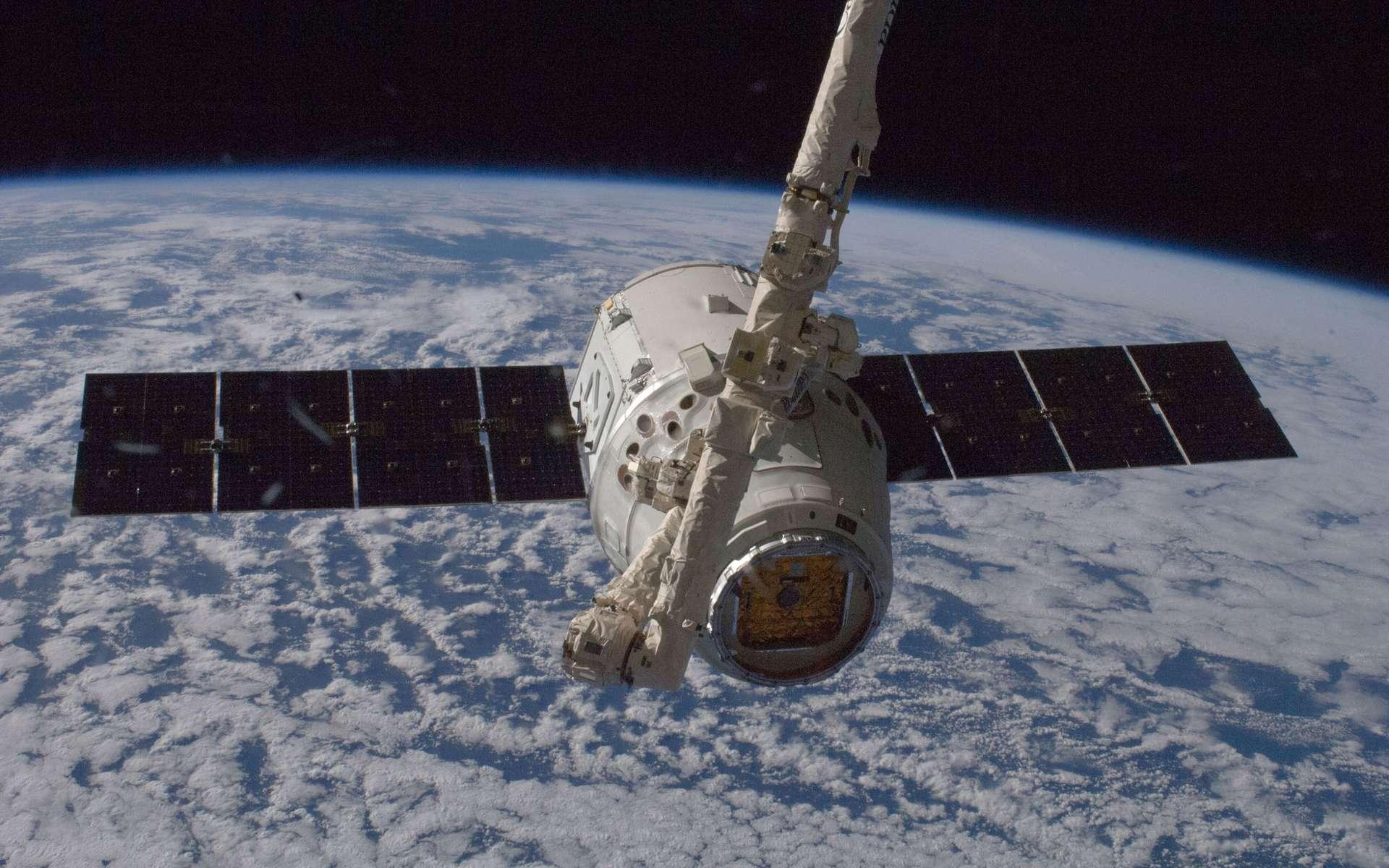 Une capsule Dragon capturée par le bras robotique de la Station spatiale internationale pour être amarrée à son module Harmony. © Nasa