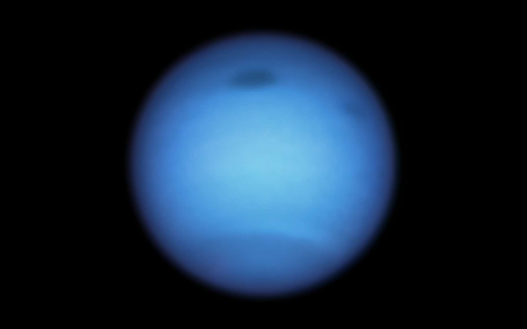 Dans l'atmosphère de Neptune, un vortex géant — en haut au centre de la planète sur cette image — se dirigeait tranquillement vers l'équateur lorsqu'il a soudainement fait demi-tour pour repartir vers le nord. © Nasa, ESA, STScI, M.H. Wong (Université de Californie, Berkeley), et L.A. Sromovsky et P.M. Fry (Université du Wisconsin-Madison)