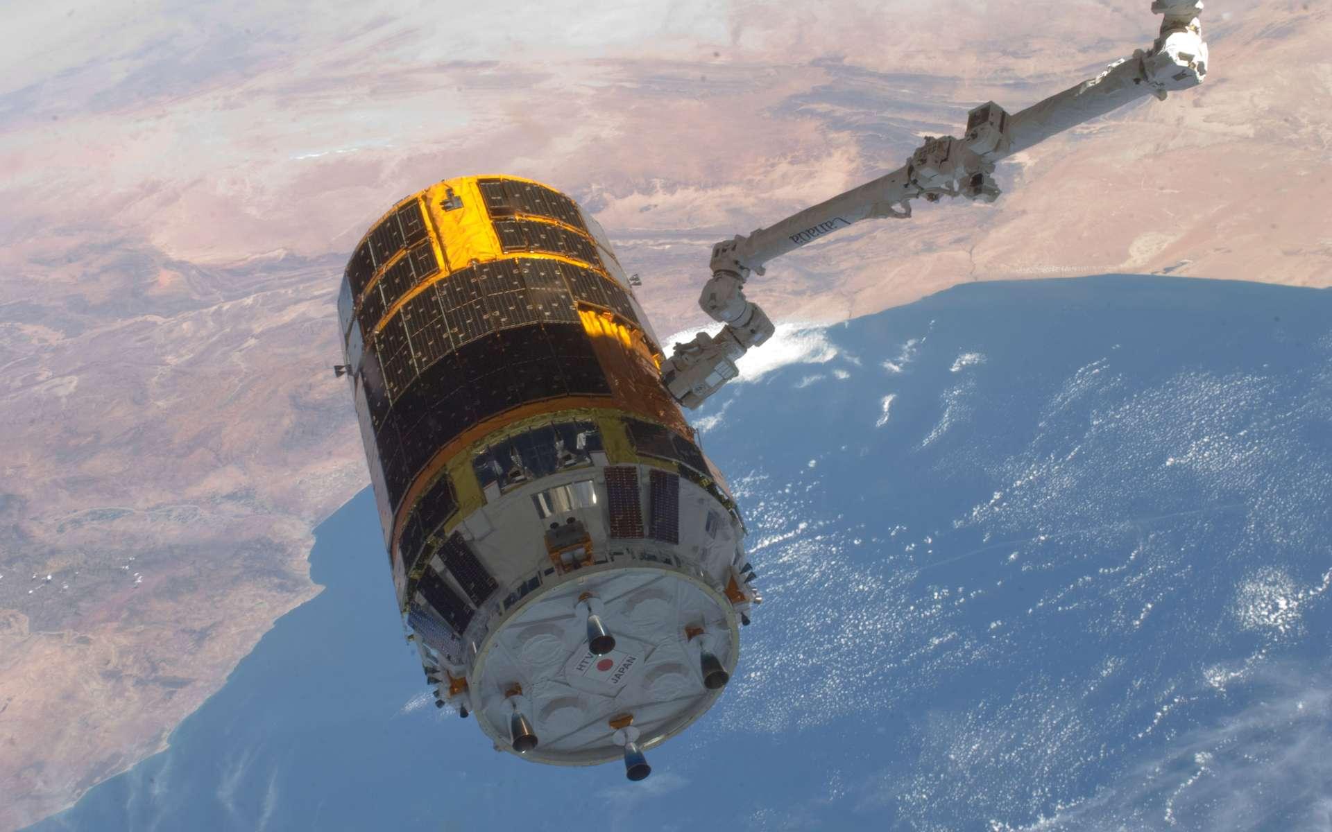 À la différence de l'ATV européen, le cargo spatial du Japon n'est pas autonome pour s'amarrer et se décrocher de la Station spatiale. Pour cela, il doit utiliser le bras robotique Canardarm2 de l'ISS, comme le montre cette photo réalisée le jour de la séparation de l'HTV-3. © Nasa