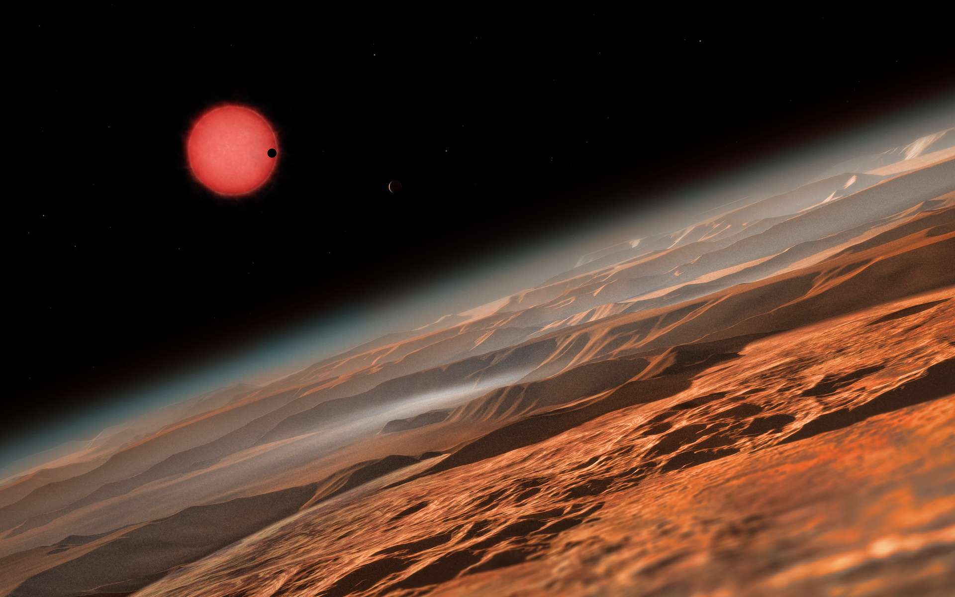 Une vue d'artiste depuis les environs d'une des trois planètes en orbite autour de l'étoile Trappist-1, une naine rouge très froide située à seulement 40 années-lumière de la Terre. Ce sont les premières planètes découvertes autour d'une telle étoile si petite et si peu lumineuse. Sur l'image, l'une des planètes internes passe devant le disque de sa petite et peu lumineuse étoile. © ESO, M. Kornmesser