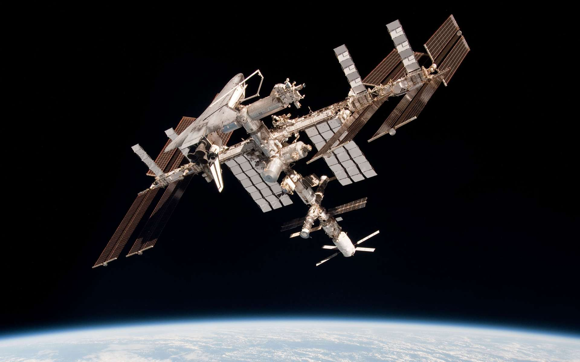 La Station spatiale internationale avec de nombreux véhicules de transport amarrés, dont l'ATV et la navette qui ne sont plus en service. Il faut y ajouter aujourd'hui le Dragon de SpaceX et le Cygnus d'Orbital ATK et, demain, la version habitée du Dragon et le Starliner de Boeing, sans oublier un module gonflable en test et un port d'amarrage de secours. L'ISS commence à évoquer un ordinateur qui manquerait de prises USB... © Nasa