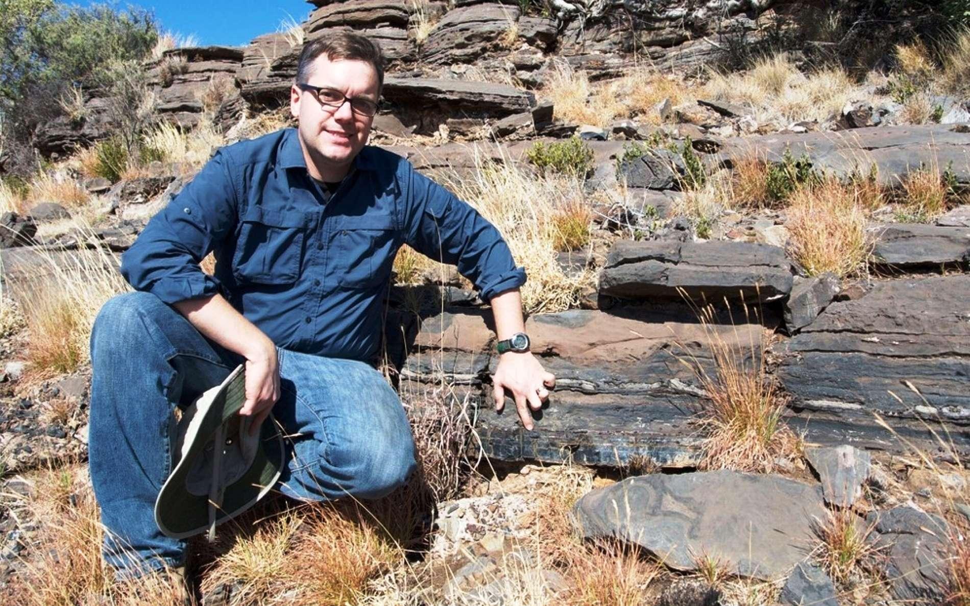 Le géologue Andrew Czaja indique la couche de roche dans laquelle des bactéries sulfureuses fossiles ont été découvertes en Afrique du Sud. © Aaron Satkoski