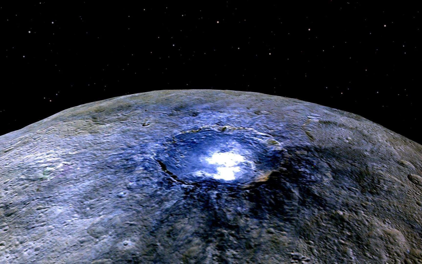 Vue en perspective du cratère Occator (90 km de diamètre) prise par Dawn à 4.400 km de la surface. L'image en fausses couleurs révèle la répartition de différents matériaux selon leur degré de réflexion de la lumière solaire. Le bleu signale la présence de composés plus brillants comme ici, les plus célèbres (et récentes?) taches blanches de Cérès. © Nasa, JPL-Caltech, UCLA, MPS, DLR, IDA
