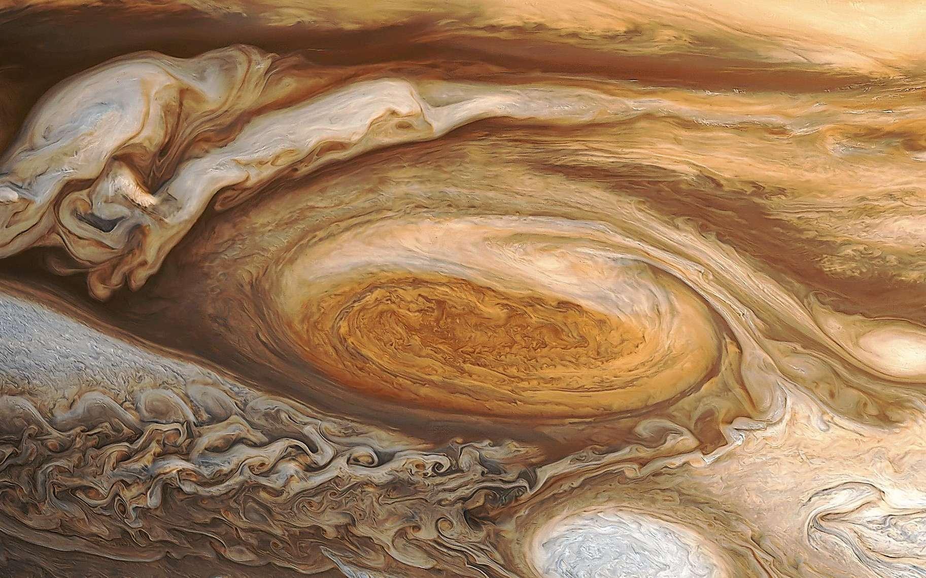 La Grande Tache Rouge de Jupiter, existant au moins depuis les observations de l'astronome Jean-Dominique Cassini au XVIIe siècle, a vu sa taille et sa couleur varier depuis le XIXe siècle. C'est à cette époque qu'elle a pris la coloration qui lui a donné son nom. Il n'y a pas de consensus sur l'origine et la nature exacte des composés chimiques à l'origine de sa couleur. On en voit ici une photographie traitée à l'ordinateur à partir des observations de Voyager 1. © Nasa