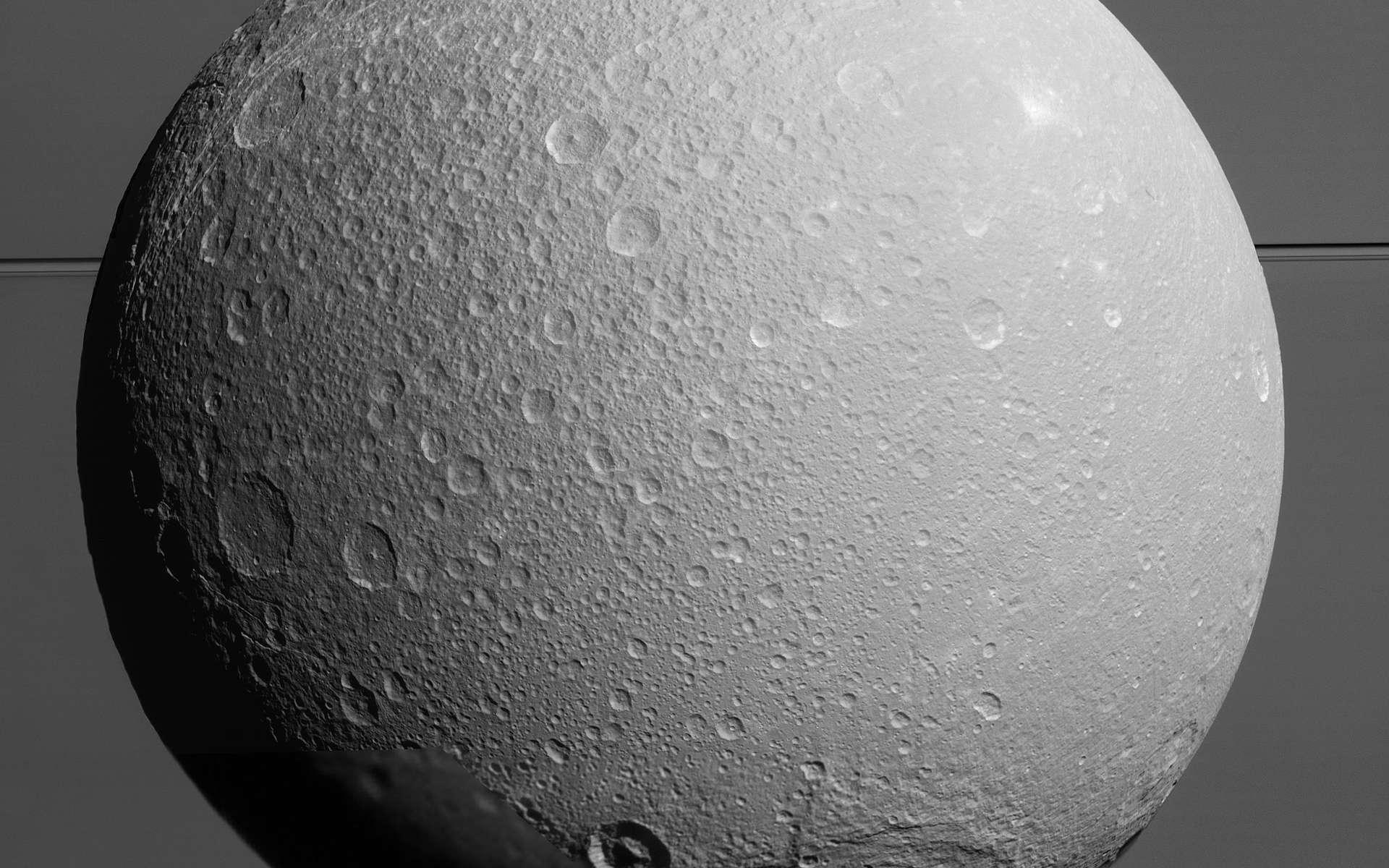 Au premier-plan, Dioné et sa surface grêlée de cratères d'impact et à l'arrière-plan, on distingue l'atmosphère de Saturne et ses anneaux. L'image a été prise par Cassini le 17 août 2015, à 170.000 km de sa surface lorsqu'elle entreprenait le dernier survol de sa mission de cette lune glacée. © Nasa, JPL-Caltech, Space Science Institute