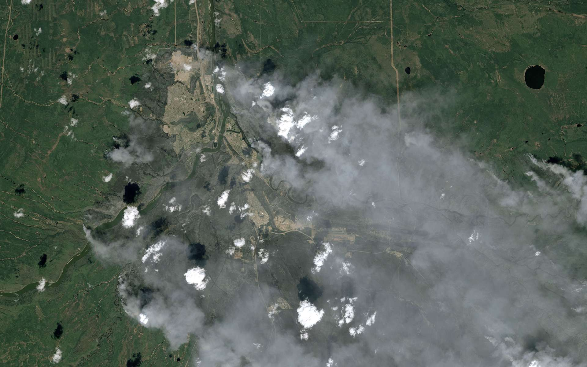 Cette image satellite, acquise par le satellite Spot 7 le 6 mai dernier, offre une grande emprise et une résolution de 1,5 mètre. Elle montre une partie de la ville de Fort McMurray, au Canada, cernée par les incendies (les zones brûlées apparaissent en gris). © Airbus DS 2016