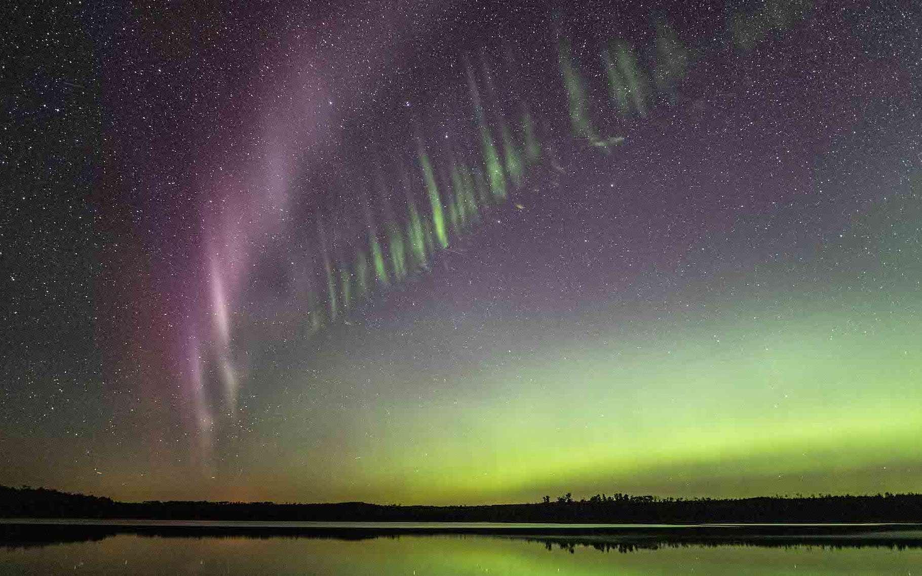 Sur cette image, on distingue parfaitement les deux composantes du phénomène Steve : une sorte de clôture à piquet verte surmontée d'un ruban violet. C'est dans la partie verte que les astronomes de la Nasa ont observé de fines stries qui pourraient les aider à résoudre le mystère de l'origine du phénomène. © Nasa