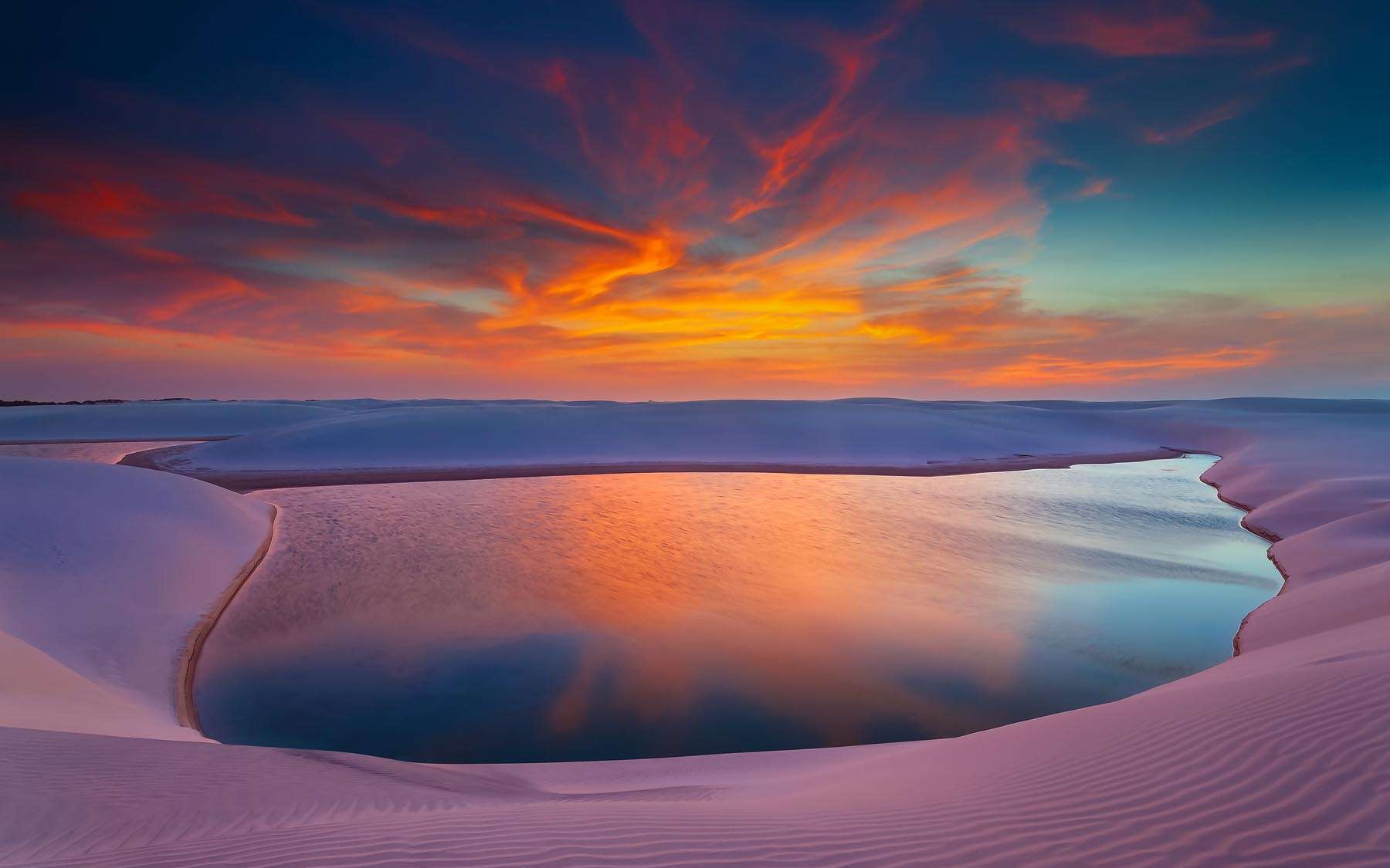 Sur la côte Atlantique, le Parc National des Lençóis Maranhenses, situé dans l'état du Maranhão, couvre une large bande au nord-est du Brésil. Ce qui ressemble à un mirage est pourtant bien réel. Au crépuscule, le soleil se reflète dans l'une des innombrables cuvettes lagunaires qui se remplissent d'eau douce à la saison des pluies. Certaines dunes peuvent atteindre 40 mètres de haut. Un instant magique sublimé par une légère saturation des couleurs.© Marcio Cabral, tous droits réservés
