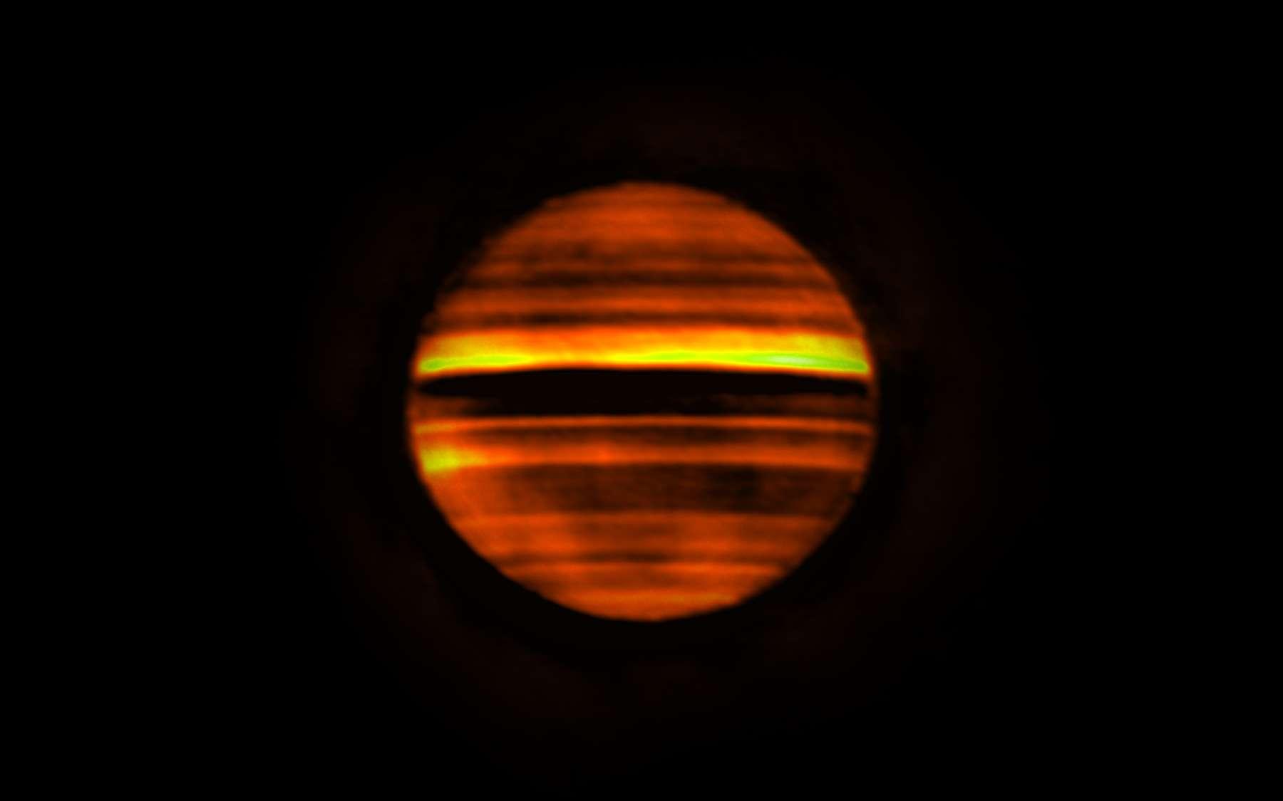 Voici en fausses couleurs une image radio de Jupiter réalisée avec Alma. Les bandes lumineuses indiquent les températures élevées et les bandes sombres les températures basses. Les bandes sombres correspondent aux zones sur Jupiter, qui sont souvent blanches aux longueurs d'onde visibles. Les bandes lumineuses correspondent aux ceintures brunes de la planète. Cette image contient plus de 10 heures de données, soit le temps que met Jupiter pour effectuer sa rotation. Par conséquent, la combinaison de ces données trahit la rotation de la planète qui a rendu les détails flous. © Alma (ESO/NAOJ/NRAO), I. de Pater et al.; NRAO/AUI NSF, S. Dagnello