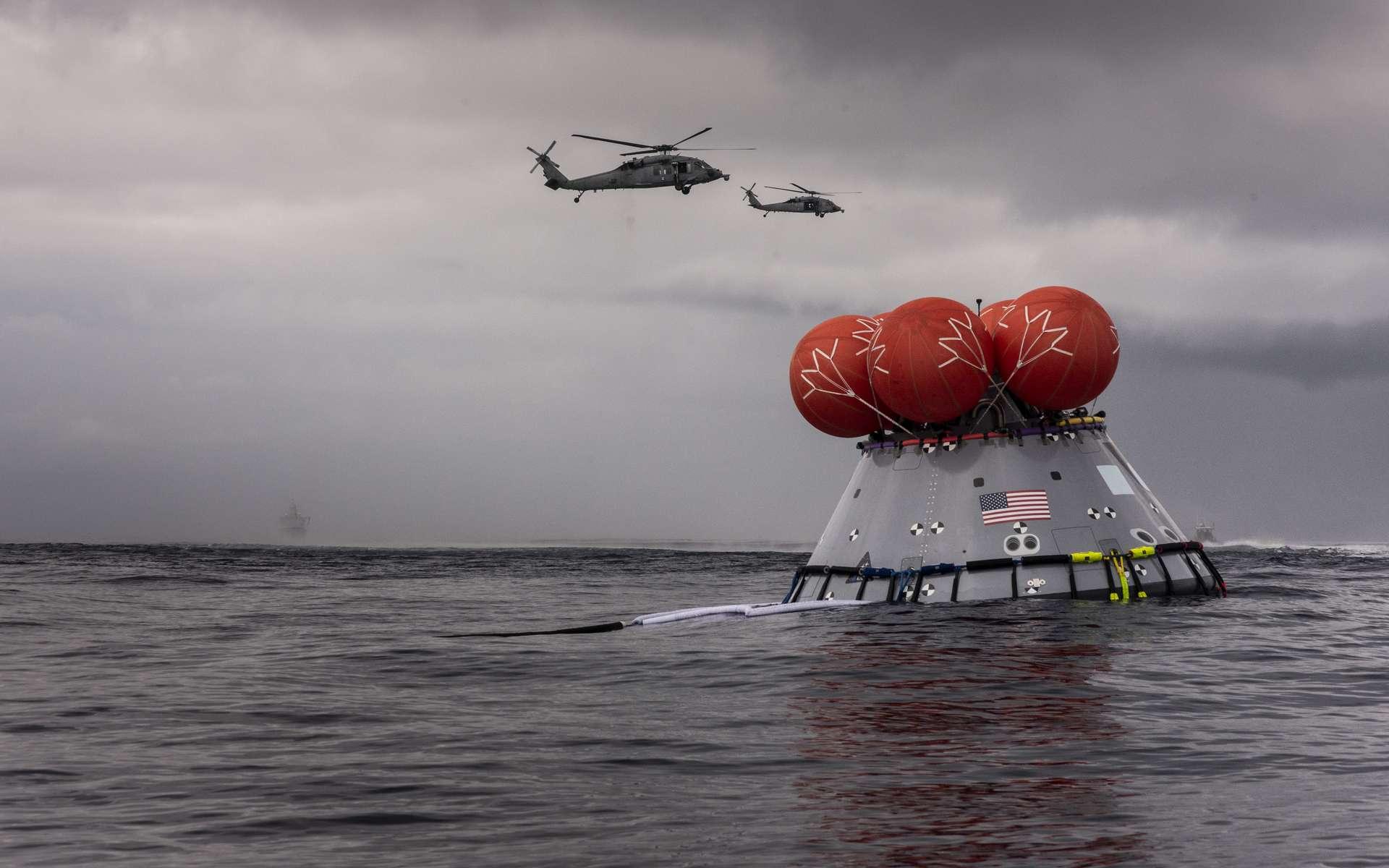 Avec l'USS John P. Murtha (LPD 26) au loin, des hélicoptères de l'escadron HSC-23 survolent une version d'essai d'une capsule Orion pendant la récupération en cours et l'essai-8 dans l'océan Pacifique. © Nasa