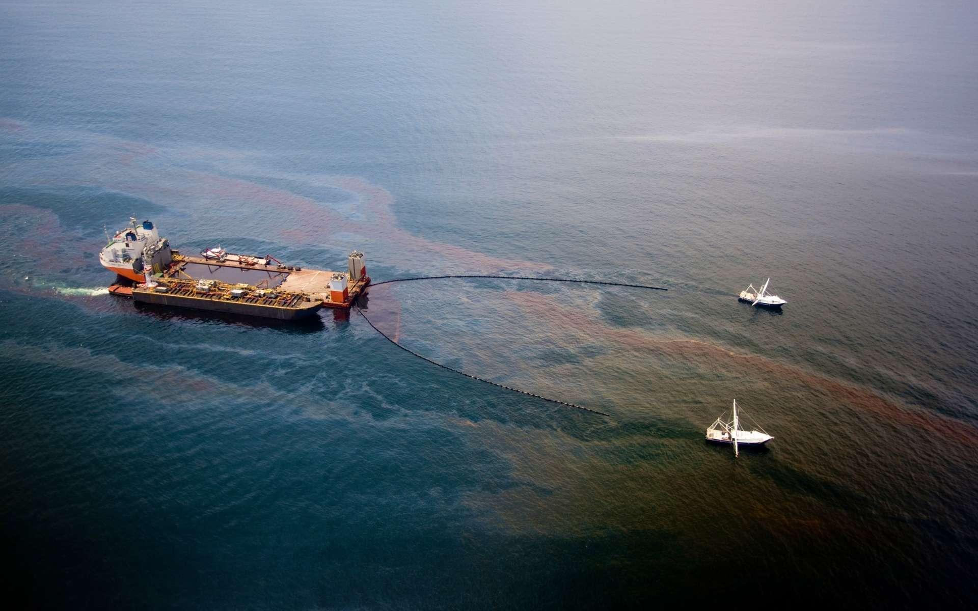 Le Mighty Servant 3, avec deux autres bateaux, en train de récolter le pétrole d'une nappe, le 18 juin 2010. Au total, environ 120 millions de litres ont été récupérés. © BP