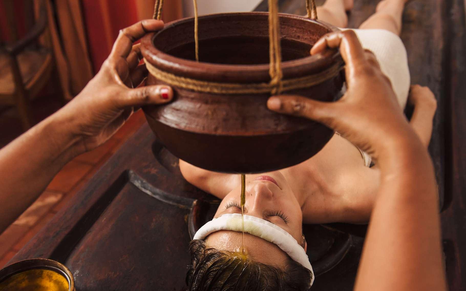 Parmi les soins prodigués lors d'une cure ayurvédique : le modelage du front par écoulement d'un filet d'huile. Il permet de diminuer l'anxiété du patient. © gilitukha, Fotolia