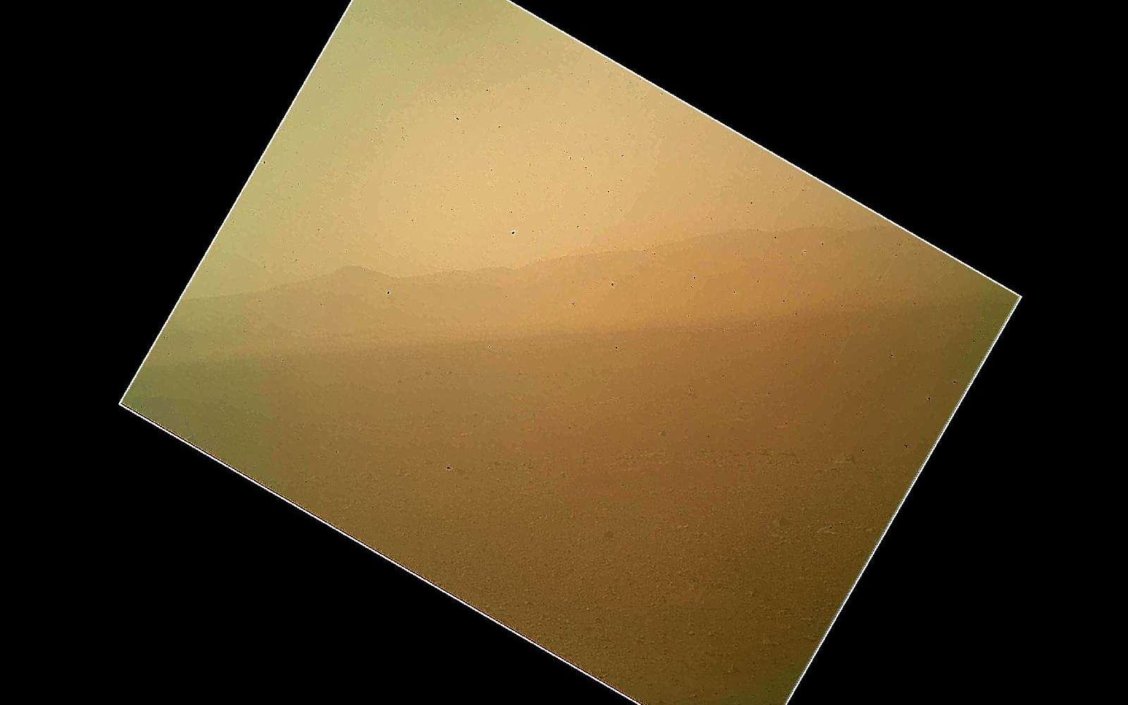 La photo ratée... Prise quelques heures après l'atterrissage par la caméra Mahli (Mars Hand Lens Imager), elle montre les parois, lointaines, du cratère Gale. Cet instrument est porté par le bras articulé, toujours en position repliée. Le flou de l'image vient de la poussière. Non, Curiosity ne s'est pas posé au milieu d'une tempête de sable. Cette poussière est celle qui s'est déposée sur le cache de l'objectif, toujours en place. Ce n'est pas un oubli, bien sûr. Transparent, il protège la caméra et permet, même fermé, ce genre de prise de vue. Quand Curiosity commencera à travailler et qu'il dépliera son bras, portant plusieurs instruments, ce cache sera retiré. © Nasa, JPL-Caltech, Malin Space Science Systems