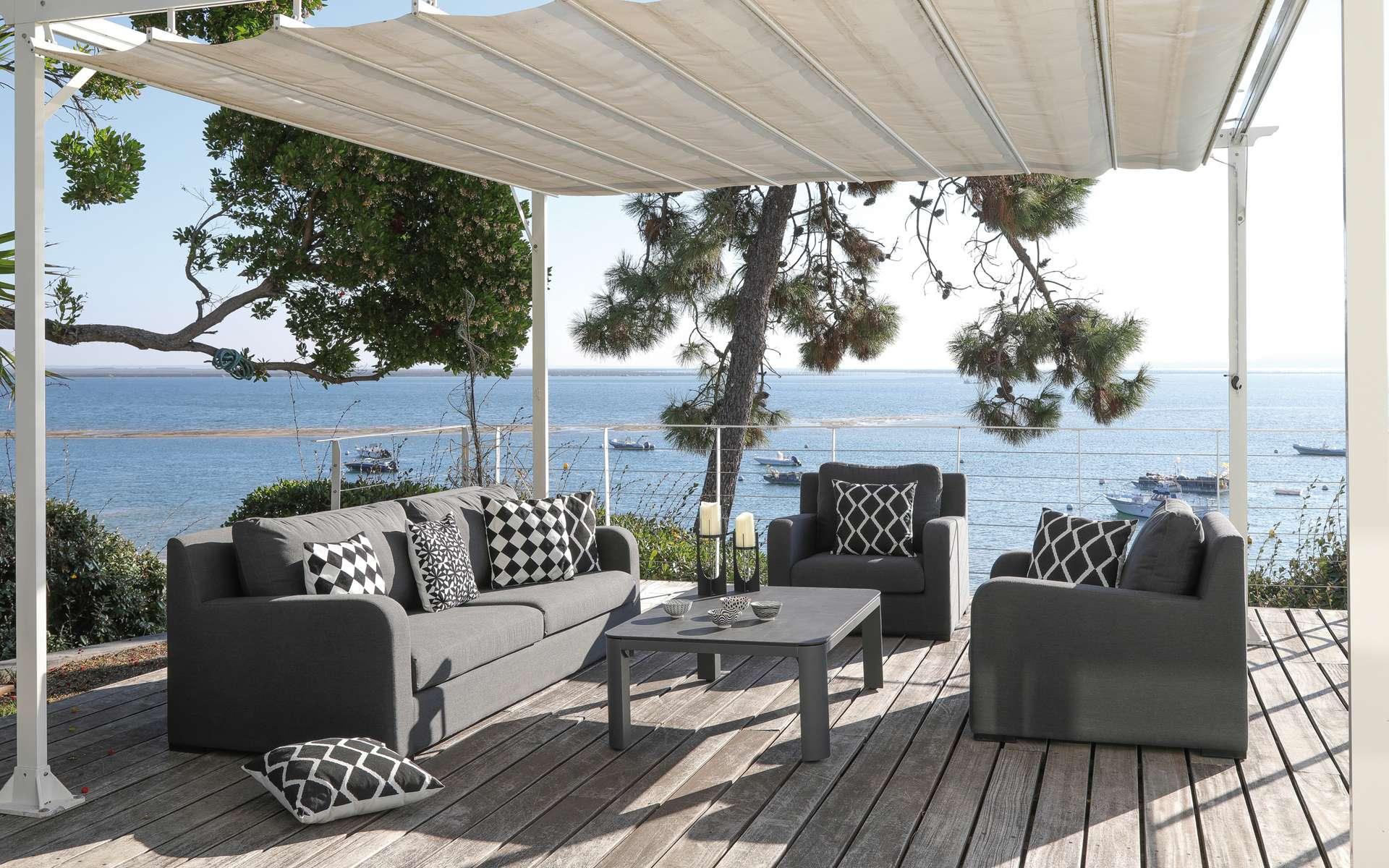 Ombragé par une tonnelle, un salon de jardin bas permet de transformer une partie de la terrasse en véritable salon extérieur. Convivialité garantie. © Proloisirs