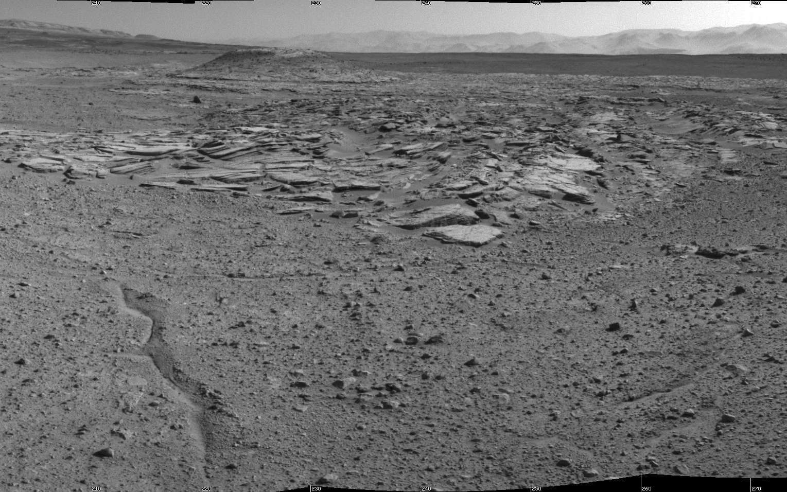 La caméra de navigation (NavCam) a pris cette mosaïque d'images le 3 avril, soit lors du 589e jour de présence de Curiosity dans le cratère Gale (sol 589). Le site qu'occupe le rover est nommé Kimberley (anciennement KMS-9), et est situé à l'intersection de quatre types de terrains. On distingue au centre de l'image des affleurements avec des roches striées. Sur l'horizon à gauche, on devine les pentes du mont Sharp. À droite s'étendent les collines qui bordent le grand cratère de 155 km de diamètre. © Nasa, JPL-Caltech