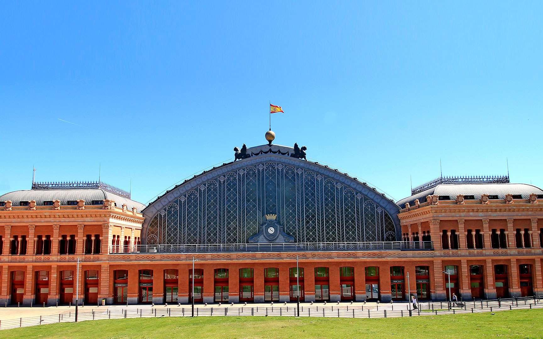 La gare d'Atocha se dresse dans la capitale de l'Espagne, Madrid. Inaugurée en 1851, elle était la première gare de Madrid et a été instaurée par la reine Isabelle II, à l'instar de deux autres gares madrilènes : Delicias et celle du Nord. Quant à la gare d'Atocha, ravagée par un incendie quelques dizaines d'années plus tard, elle a été reconstruite en fer entre 1888 et 1892. Face à l'entrée de la gare, un mémorial a été érigé en hommage aux quelque 200 personnes tuées dans l'attentat du 11 mars 2004.© Luis García, CC by-sa 4.0