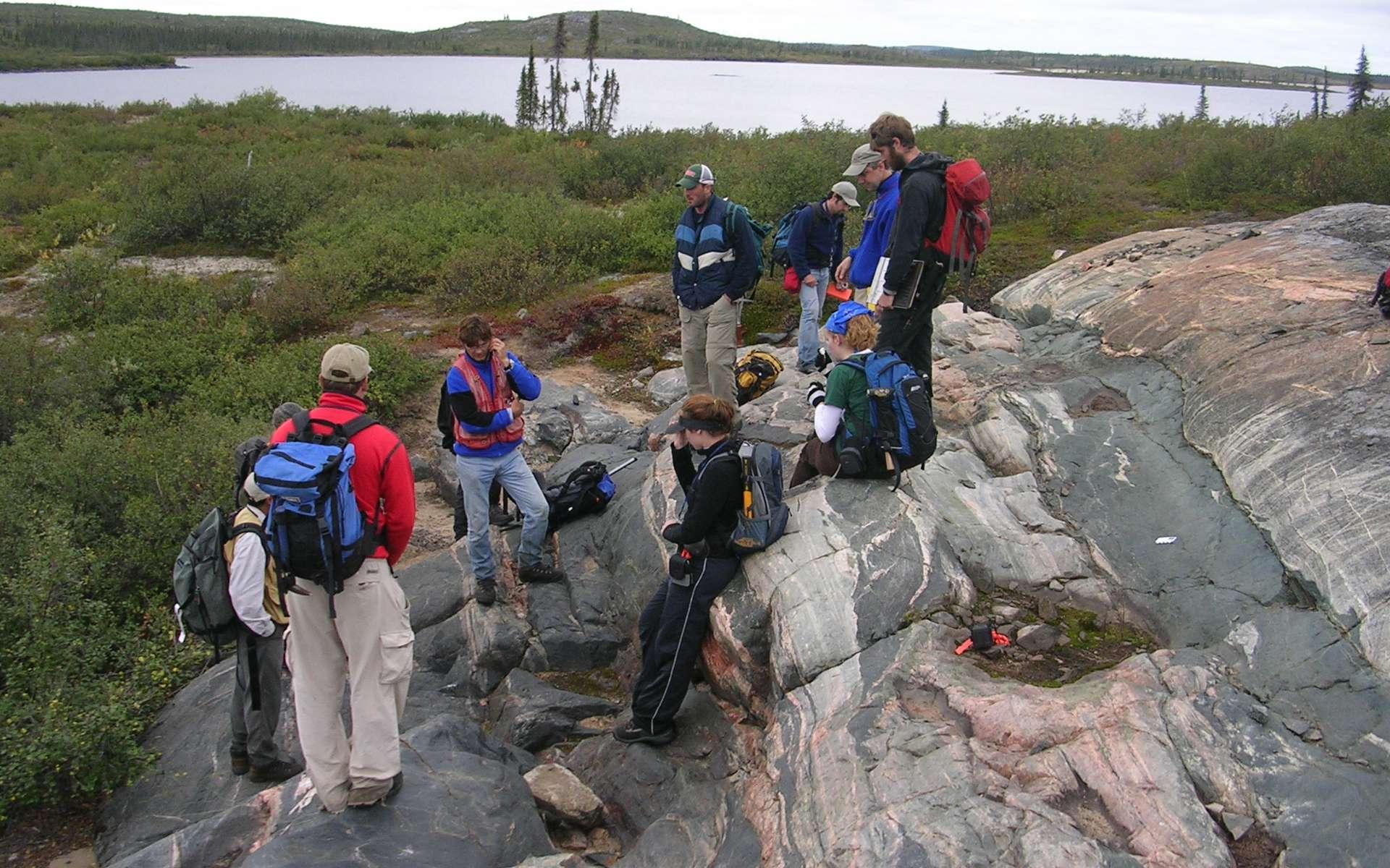 Une équipe d'étudiants en géologie examine l'affleurement rocheux de gneiss d'Acasta situé sur une île au Canada. Découvert en 1989, il tire son nom de sa proximité avec la rivière Acasta du Grand Lac de l'Ours. Ses roches ont des âges compris entre 4,03 à 3,58 milliards d'années et elles sont des vestiges de croûte continentale les plus anciens connus à ce jour. © Northwest Territories Geoscience Office