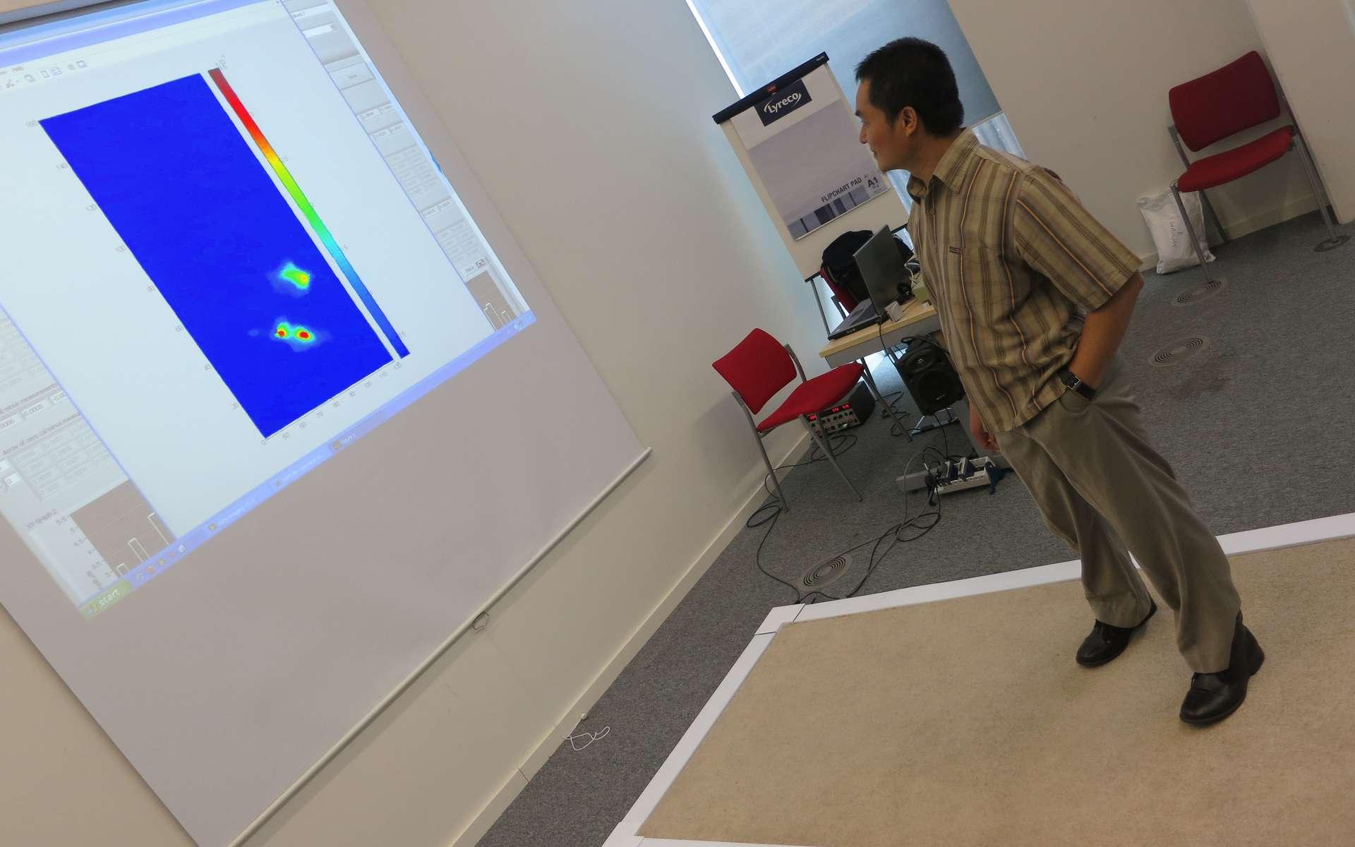 Au sol, le « tapis magique » codéveloppé par les chercheurs de l'université de Manchester et du Photon Science Institute. Lorsqu'une personne marche sur la surface, le réseau de fibres optiques relié à des capteurs placés sur les bords du tapis enregistre les informations et les transmet à un ordinateur. © Manchester University