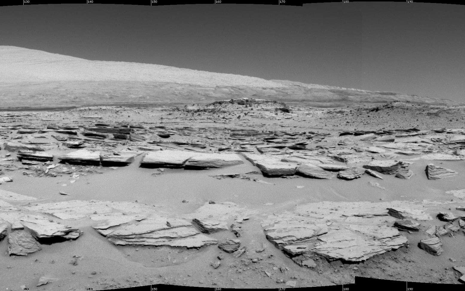 Magnifique panorama à 160° réalisé par la caméra de navigation (Navcam) de Curiosity, au 548e jour de sa mission. L'image (projection cylindrique) est centrée sur la direction sud-sud-est. Au premier plan, on distingue les feuillets de roches du site Junda où le rover s'est arrêté durant quelques heures, le 19 février. Haut de 5.500 mètres, le mont Sharp (également appelé Aeolis Mons, soit le mont Éole) domine majestueusement l'horizon. © Nasa, JPL-Caltech