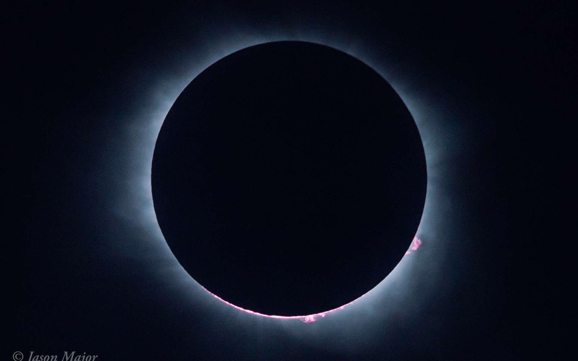 Le Soleil et la Lune au moment de la totalité en Caroline du Sud. Du disque noir ne dépassent que les protubérances solaires. Les deux astres alignés sont nimbés de la couronne solaire. © Jason Major, lightsinthedark.com
