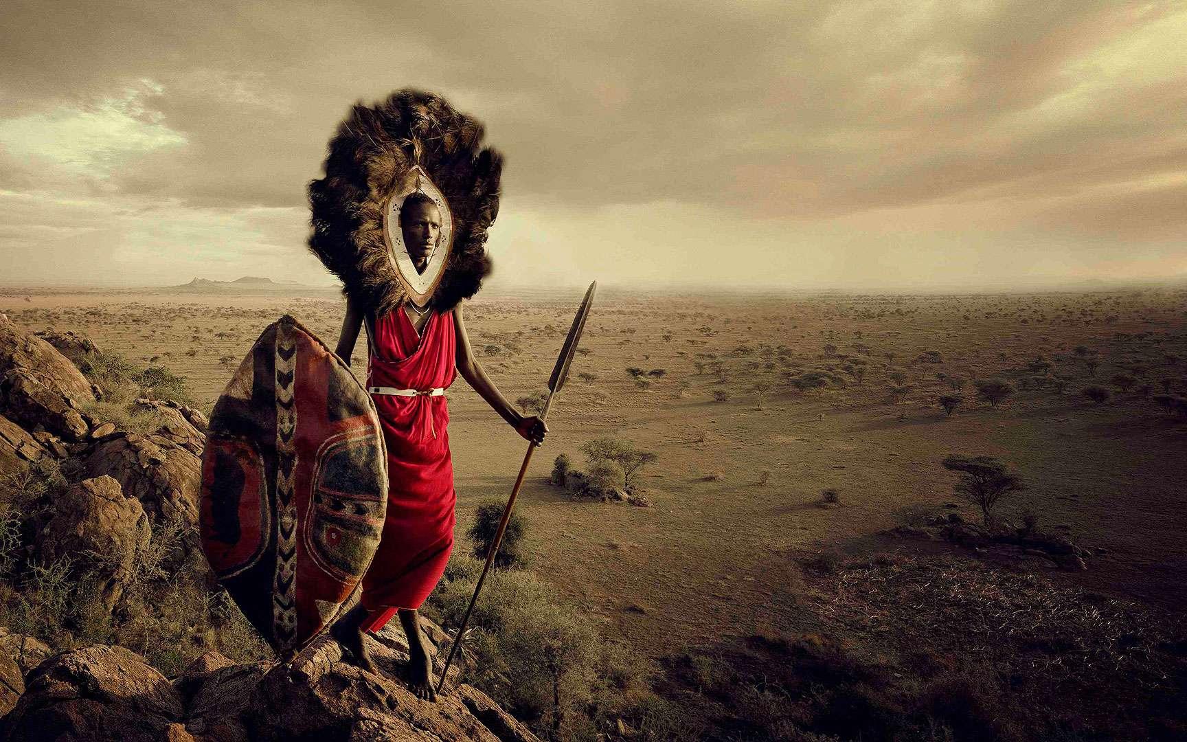 Les Massaïs - Tanzanie. Être né Massaï, c'est appartenir à l'une des dernières grandes cultures guerrières au monde. Tout petit, le jeune Massaï doit apprendre les pratiques culturelles, les lois coutumières et les responsabilités qu'il devra assumer à l'âge adulte. Ils sont célèbres pour l'aduma, une danse durant laquelle les jeunes hommes exécutent les pieds joints de grands bonds pour démontrer leur force et vigueur en tant que guerriers. Nomades, ils suivent le régime des précipitations en quête de nourriture et d'eau pour leurs troupeaux. La richesse, chez eux, se mesure à la taille du cheptel et au nombre d'enfants. Ils vivent dans des huttes appelées kraal ou boma, construites en semi-dur à partir de boue, branches, herbes et bouse de vache. Ils portent de nombreux bijoux aux bras, pieds, cou et les femmes se rasent le crâne et se font arracher deux incisives sur la mâchoire inférieure. © Jimmy Nelson. Tous droits réservés