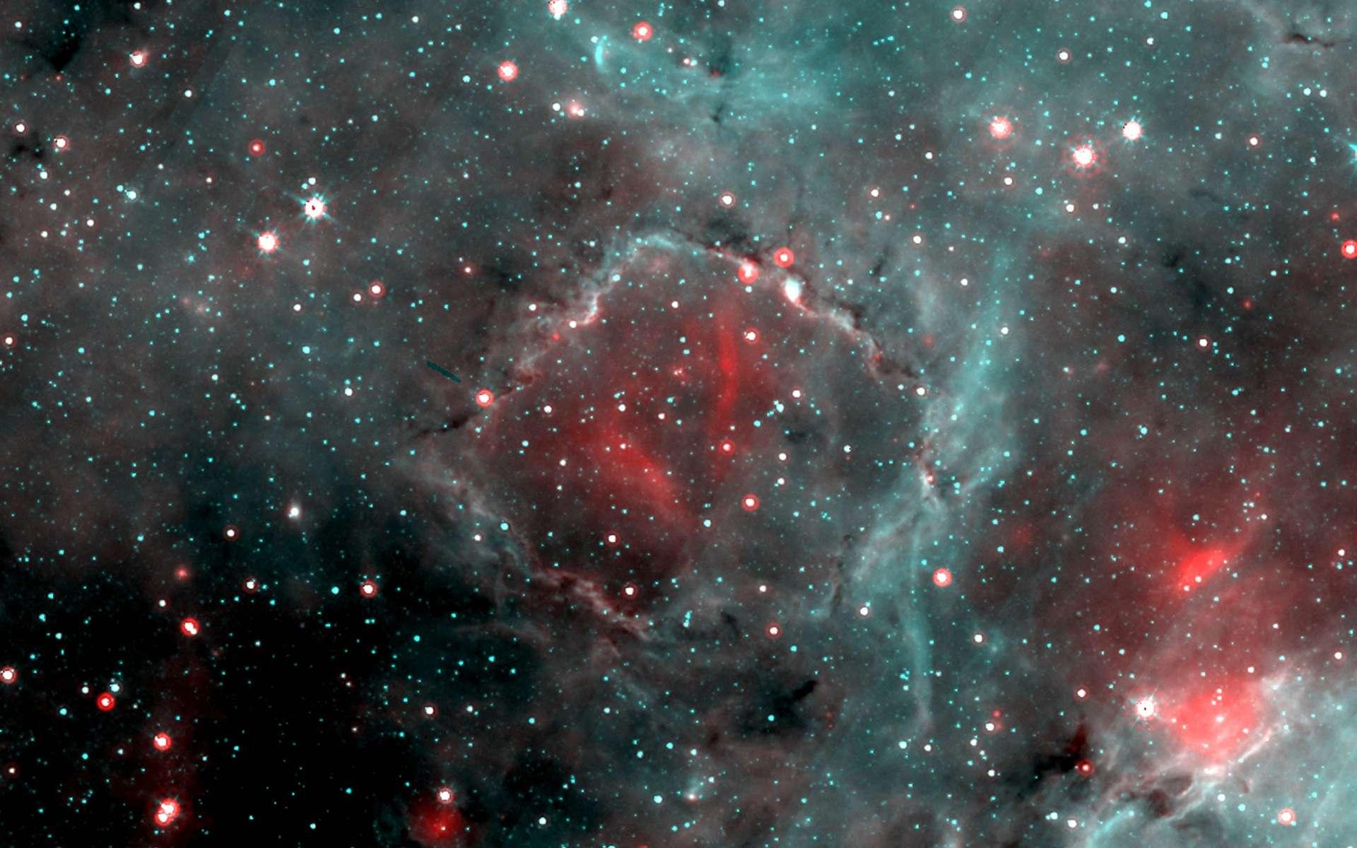 On voit ici une image de la « bulle carrée », G15.68-0.28. Elle résulte de la composition de deux images obtenues par le satellite Spitzer à 24 microns (rouge) et 8 microns (turquoise). L'émission étendue à 8 microns provient essentiellement de petits grains ou de grosses molécules, des hydrocarbures polycycliques aromatiques, excitées par le rayonnement. L'émission étendue à 24 microns provient de poussières chaudes mélangées au gaz ionisé. Ces poussières chaudes se trouvent aussi dans les disques et les enveloppes entourant de jeunes objets stellaires ou dans les enveloppes d'étoiles évoluées. © Laboratoire d'Astrophysique de Marseille