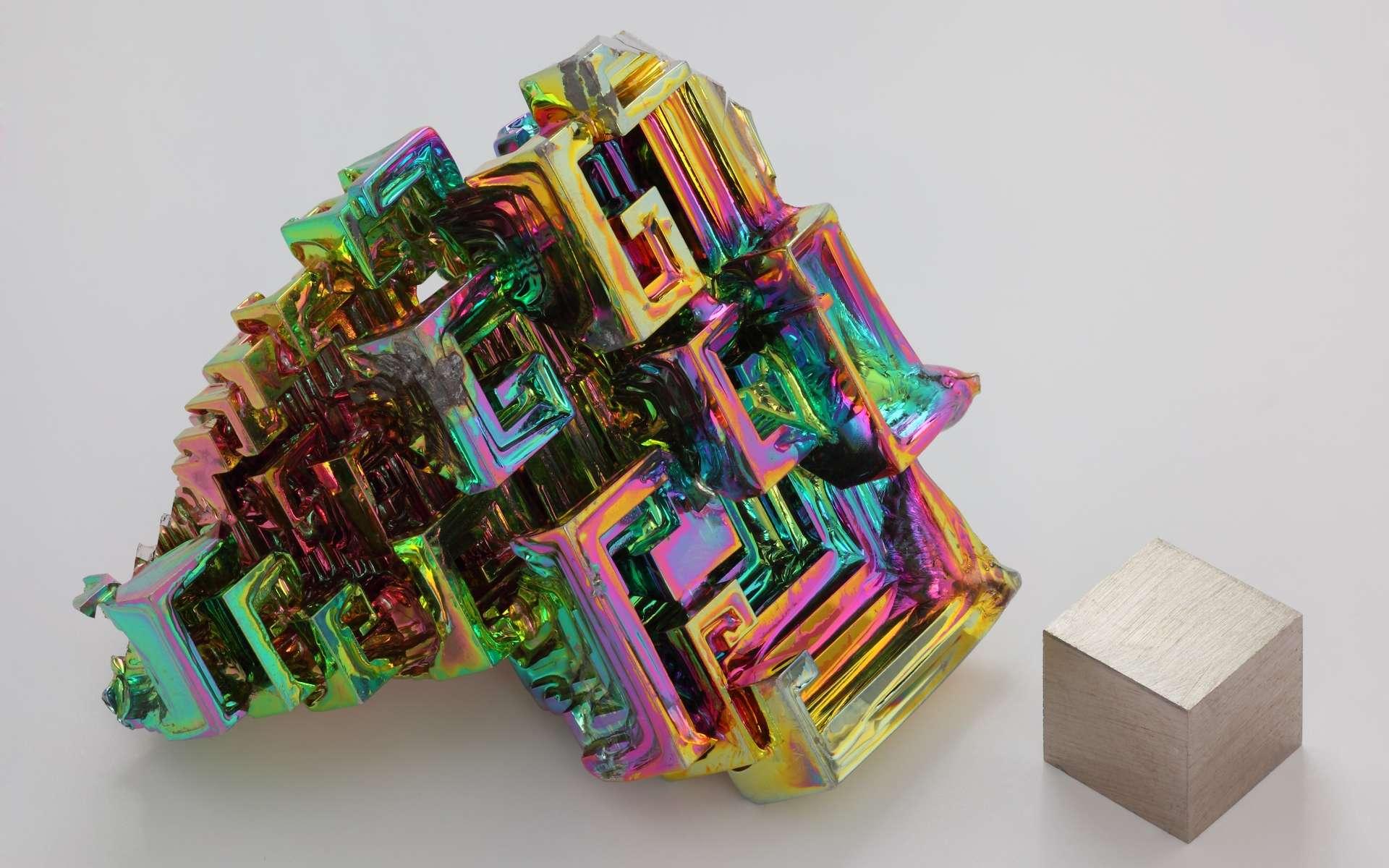 Le bismuth défie la théorie de la supraconductivité. Ici, cristal obtenu par cristallogenèse artificielle de bismuth métallique à côté d'un cube d'1 cm3 de bismuth pur à 99,99 %, pour comparaison de taille. L'irisation est due à une couche d'oxyde très mince. © Alchemist-hp, Wikipédia, CC by-sa 3.0