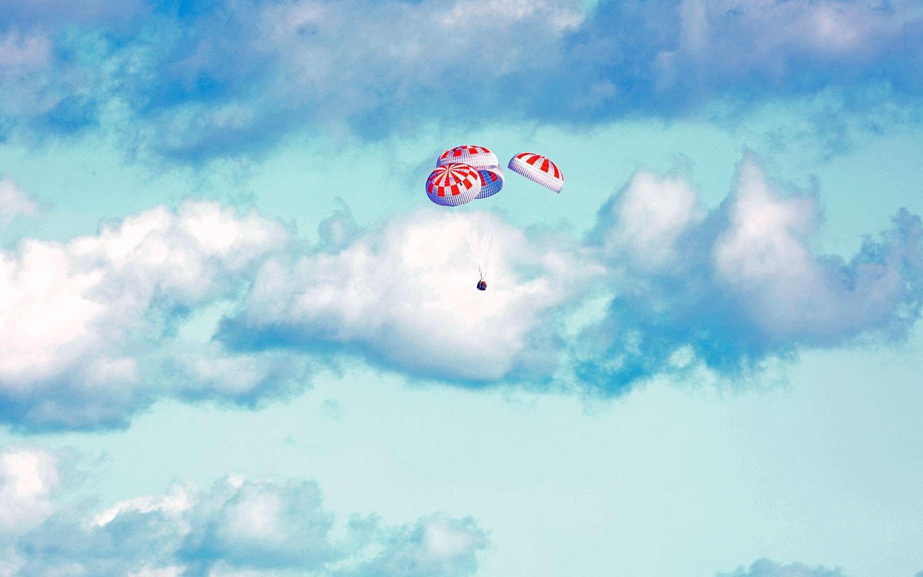 La Crew Dragon et ses quatre immenses parachutes, quelques instants avant son amerrissage sur l'océan Atlantique. © Nasa, Cory Huston